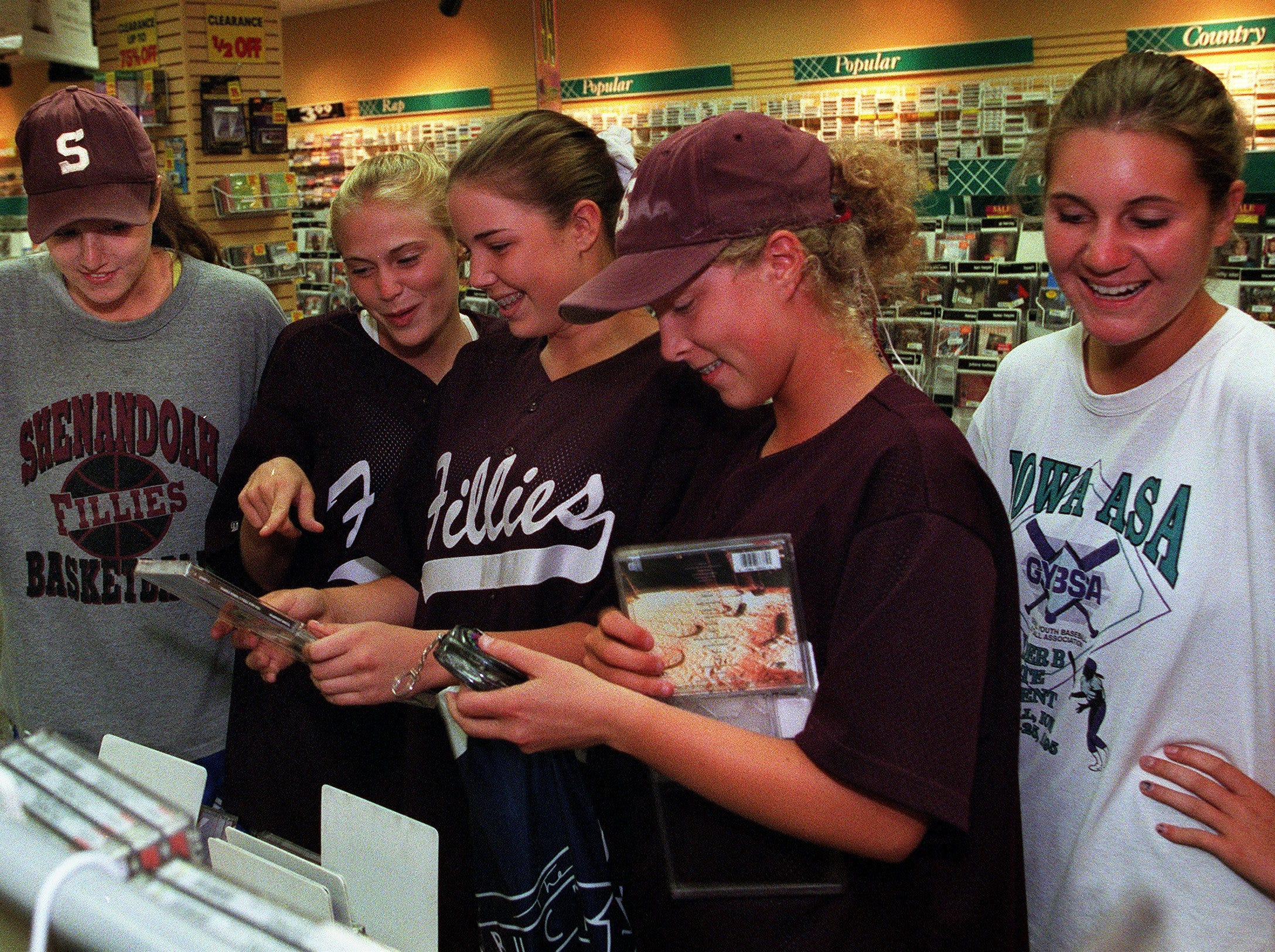 "Some members of the Shenandoah Fillies softball team got some shopping time during a recent tournament. Katie Almeida, 15, is left, Jessica Taeachout, 15, Ashley Christiansen, 14, Nicki Bryson, 17, and Jamie Brink, 14 check out CDs at Sam Goody in Valley West Mall. ""We don't have a mall in Shenandoah, so this is a big deal for us,"" said Katie Almeida on July 4, 1998."