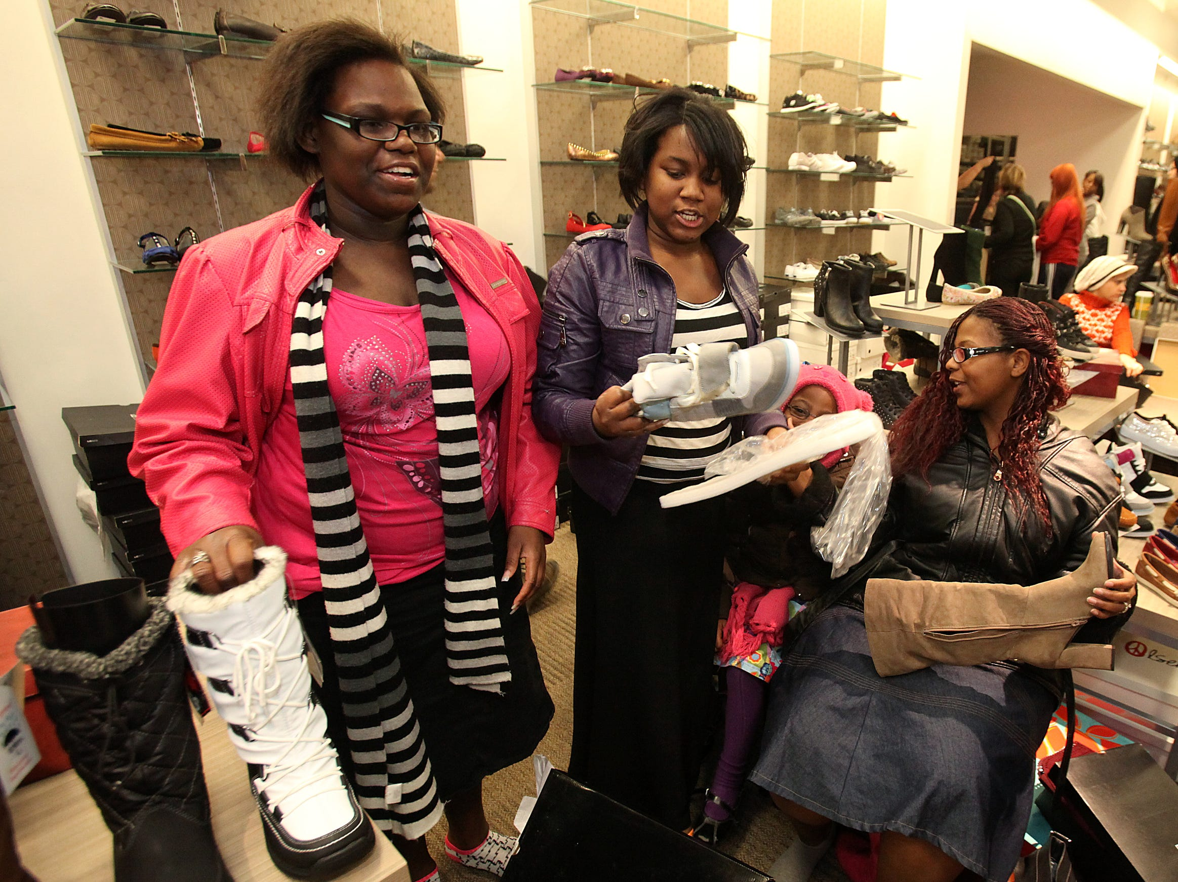 Destiny Philpot, left, and her sister, Dakeyah, look over some shoes while Azariyah Mills, 6, and Matanyah Lee (seated) look over a pair of boots while shopping at Valley West Mall on Nov. 24, 2012.