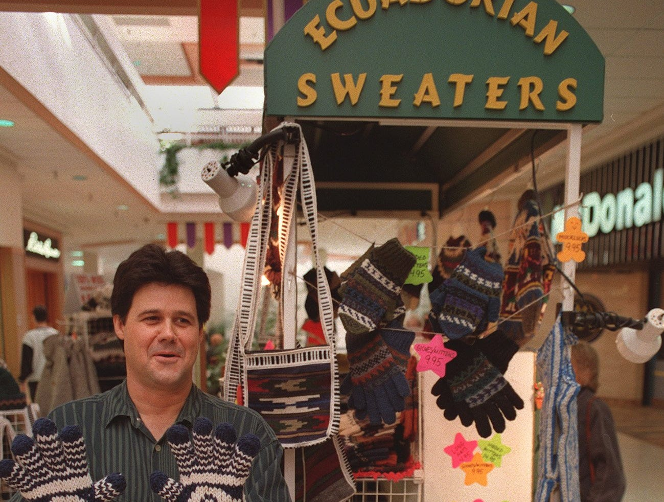 Thomas Gillham shows off warm, hand-knit mittens from Ecuador at his Caravan International temporary kiosk on the bottom level of Valley West Mall on Nov. 17, 1997.