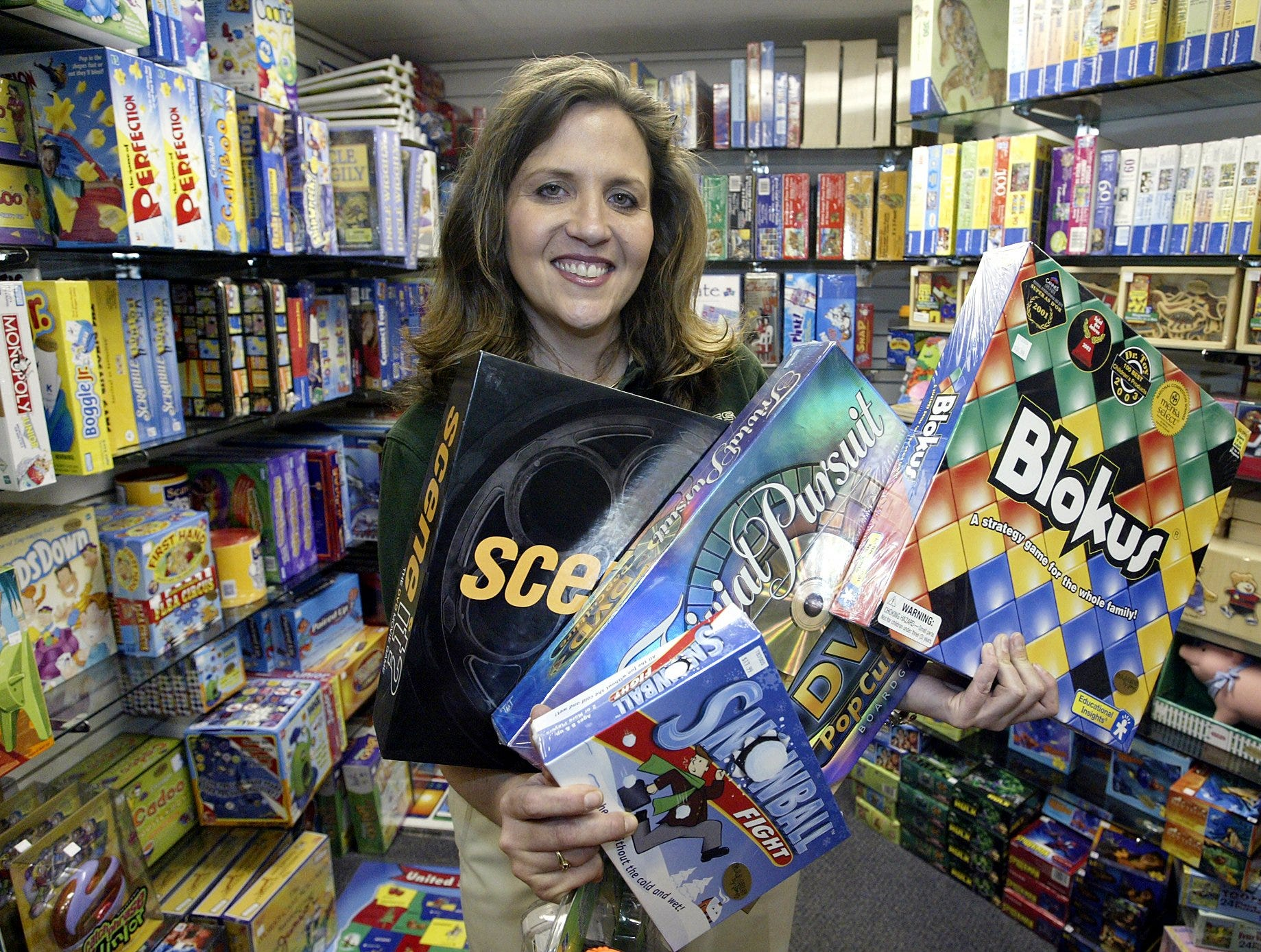 Corinne Harrison, manager of Games by James, holds some of the stores most popular games at the store in the Valley West Mall in West Des Moines on Wednesday, Dec. 31, 2003.