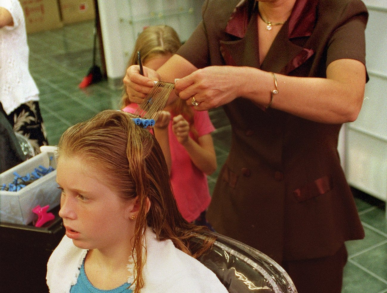 Sun Ok Kramer, owner of Sunny's Sons Salon at Valley West Mall, works on the hair style of Magen Carr, 9. Shot on August 19, 1999.