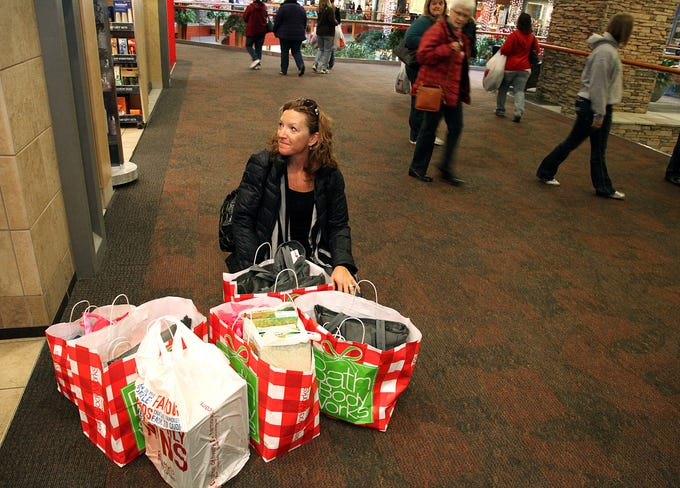 Nancy Eveland of Osage Beach, Missouri, doesn't have enough hands to carry all of her shopping bags at Valley West Mall on Nov. 24, 2012.