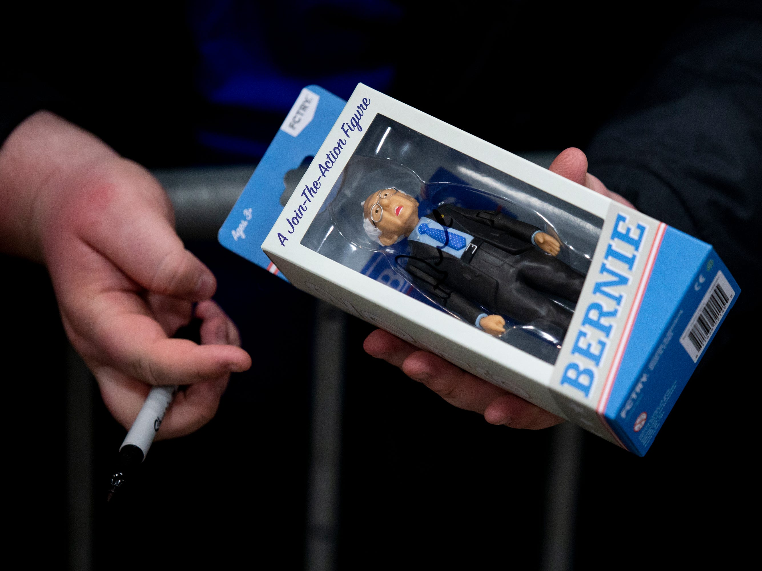 A man holds a Sen. Bernie Sanders, I-VT, action figure during Sanders' first rally in Iowa after announcing he'll run for president for the second time, on Thursday, March 7, 2019, in Council Bluffs.
