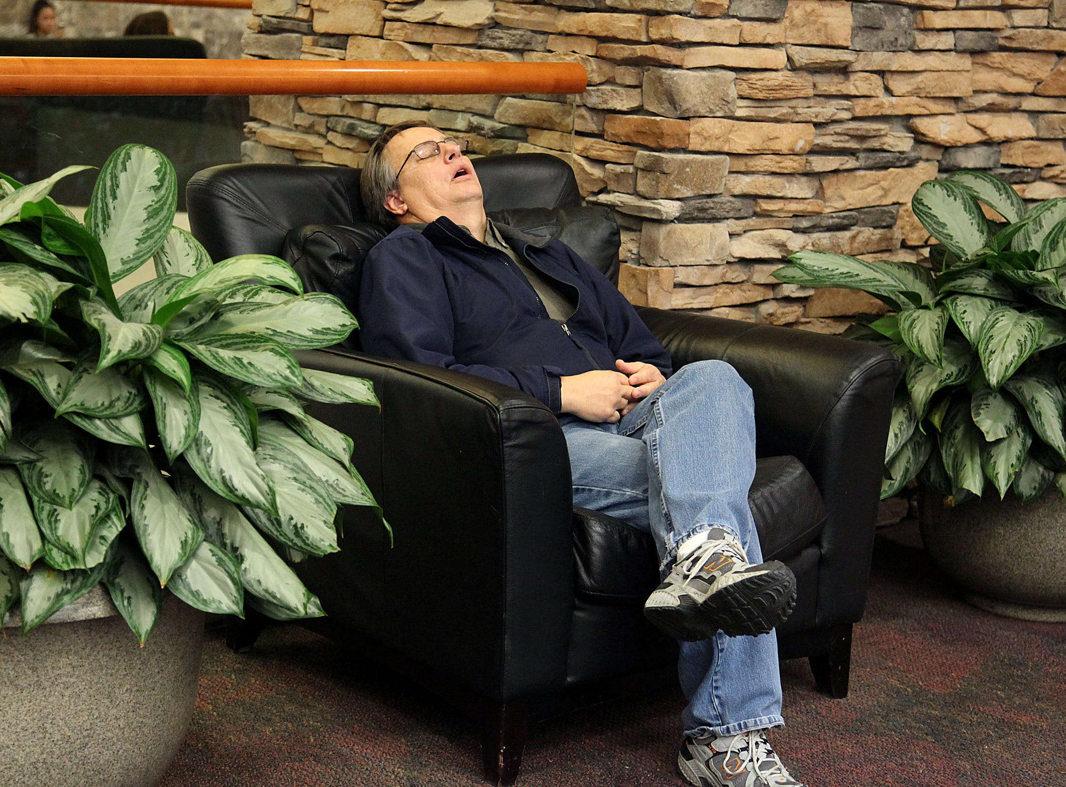 Cliff Jones of Centerville takes a brief nap while his wife shops at Valley West Mall on Nov. 12, 2012.