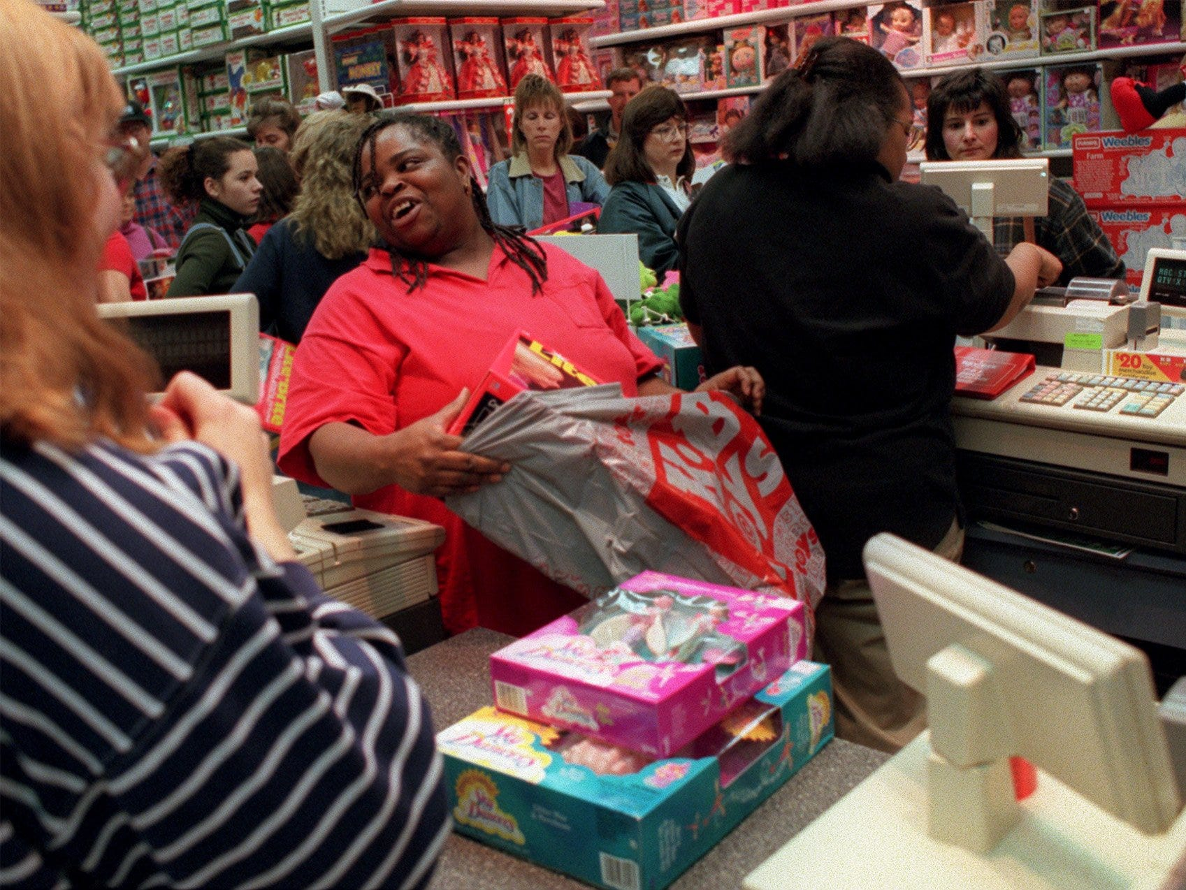 Jannetta Washington, an employee for K.B. Toys at Valley West mall uses laughter and good humor to get her through the most hectic shopping day of the year on Nov. 28, 1997.