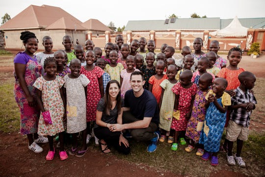 Detroit Tigers pitcher Matthew Boyd and his wife, Ashley, pose with children  in Uganda, where the Boyds opened a non-profit, Kingdom Home, and are trying to end child sex slavery.