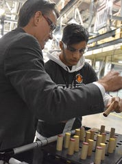 Macomb County Executive Mark Hackel works with a student at the 2018 Manufacturing Day event held at Fiat Chrysler's Warren Truck Plant on Oct. 4.