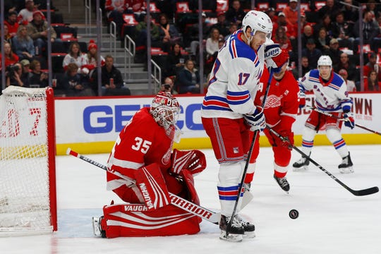 New York Rangers right wing Jesper Fast tries to redirect a shot at Detroit Red Wings goaltender Jimmy Howard during the first period March 7, 2019, in Detroit.