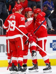 Detroit Red Wings' Tyler Bertuzzi, second from right, celebrates his goal with Madison Bowey, right, and Anthony Mantha (39) during the second period of an NHL hockey game against the New York Rangers, Thursday, March 7, 2019, in Detroit.