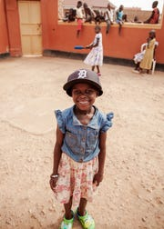 A young girl wears a Detroit Tigers hat in Uganda, where Tigers pitcher Matthew Boyd and his wife, Ashley, are trying to end child sex slavery.