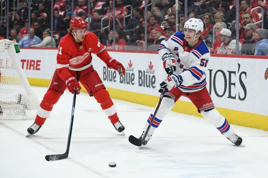 New York Rangers center Lias Andersson (50) clears the puck around Detroit Red Wings center Jacob de la Rose (61) during the first period at Little Caesars Arena on Thursday, March 7, 2019, in Detroit.