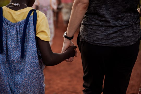 Ashley Boyd, wife of Detroit Tigers pitcher Matthew Boyd, holds the hand of a young girl in Uganda, where the Boyds have opened a non-profit aimed at ending child sex slavery.