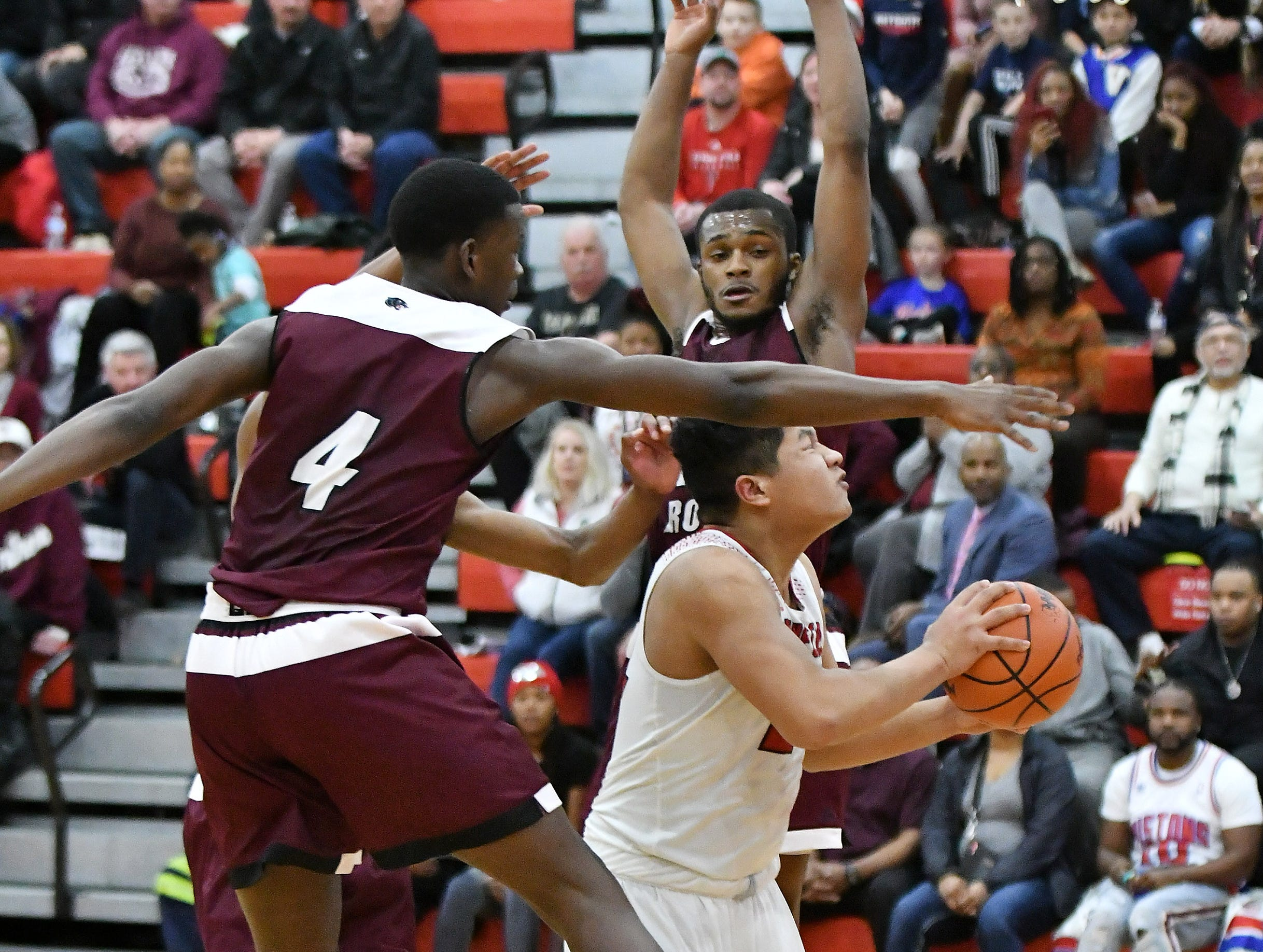River Rouge's Legen Geeter (4) and Nigel Colvin, rear, converge on Divine Child's Aeron Latham in the first half.