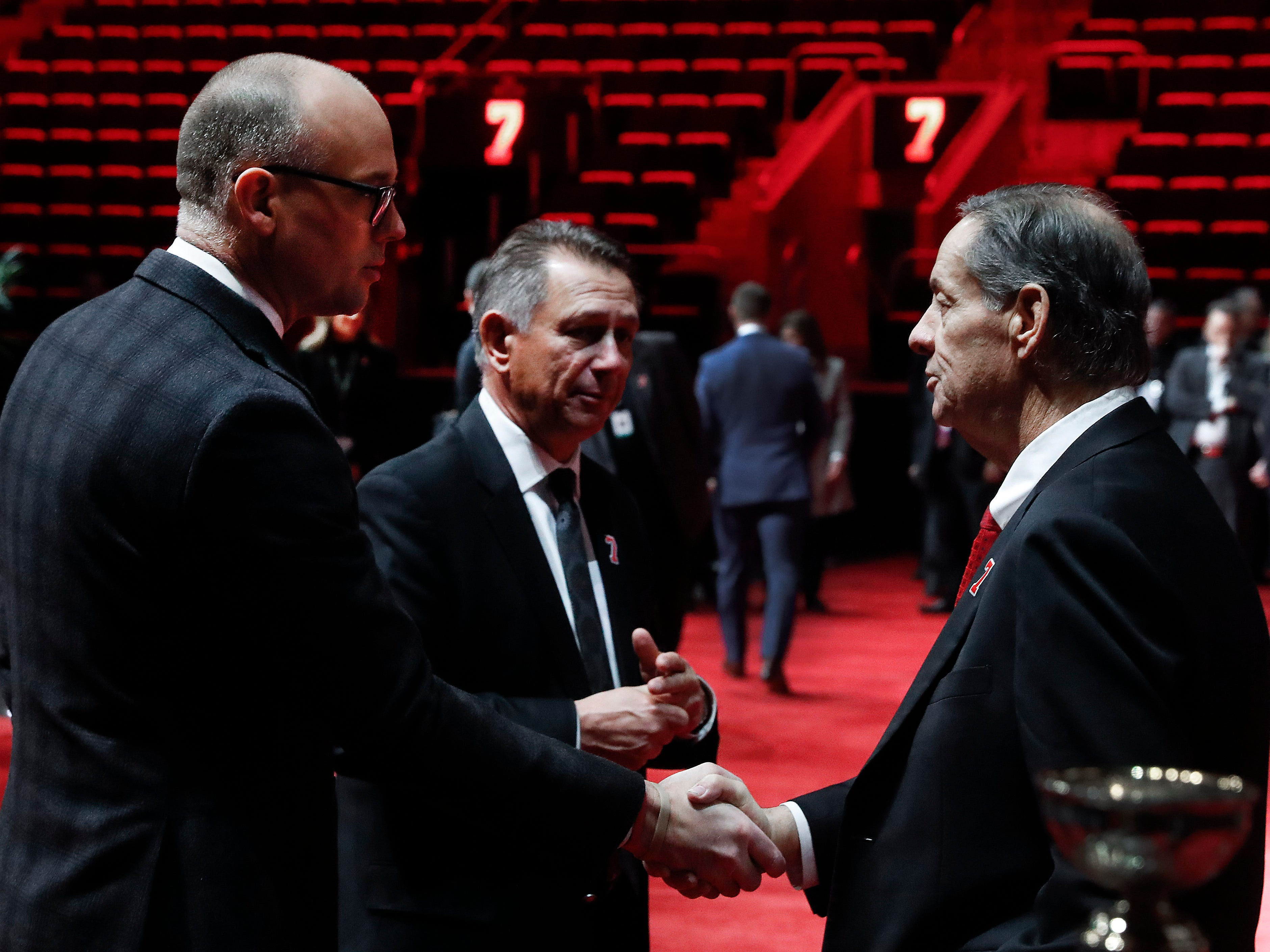 Detroit Red Wings head coach Jeff Blashill, left, and general manager Ken Holland, center, speak with Blake Lindsay, son of former player Ted Lindsay.