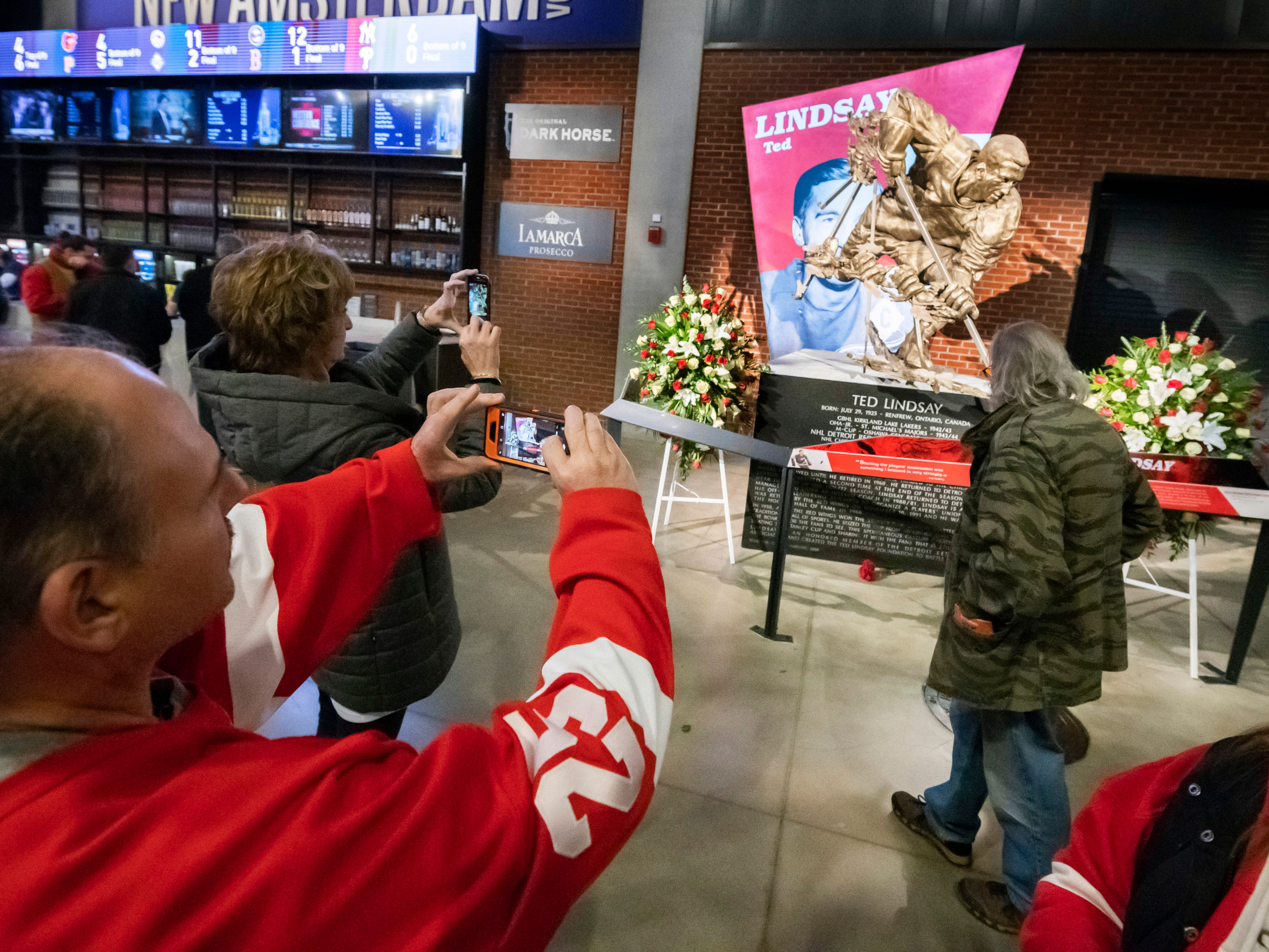 Fans take pictures of a statue of Ted Lindsay before the game.
