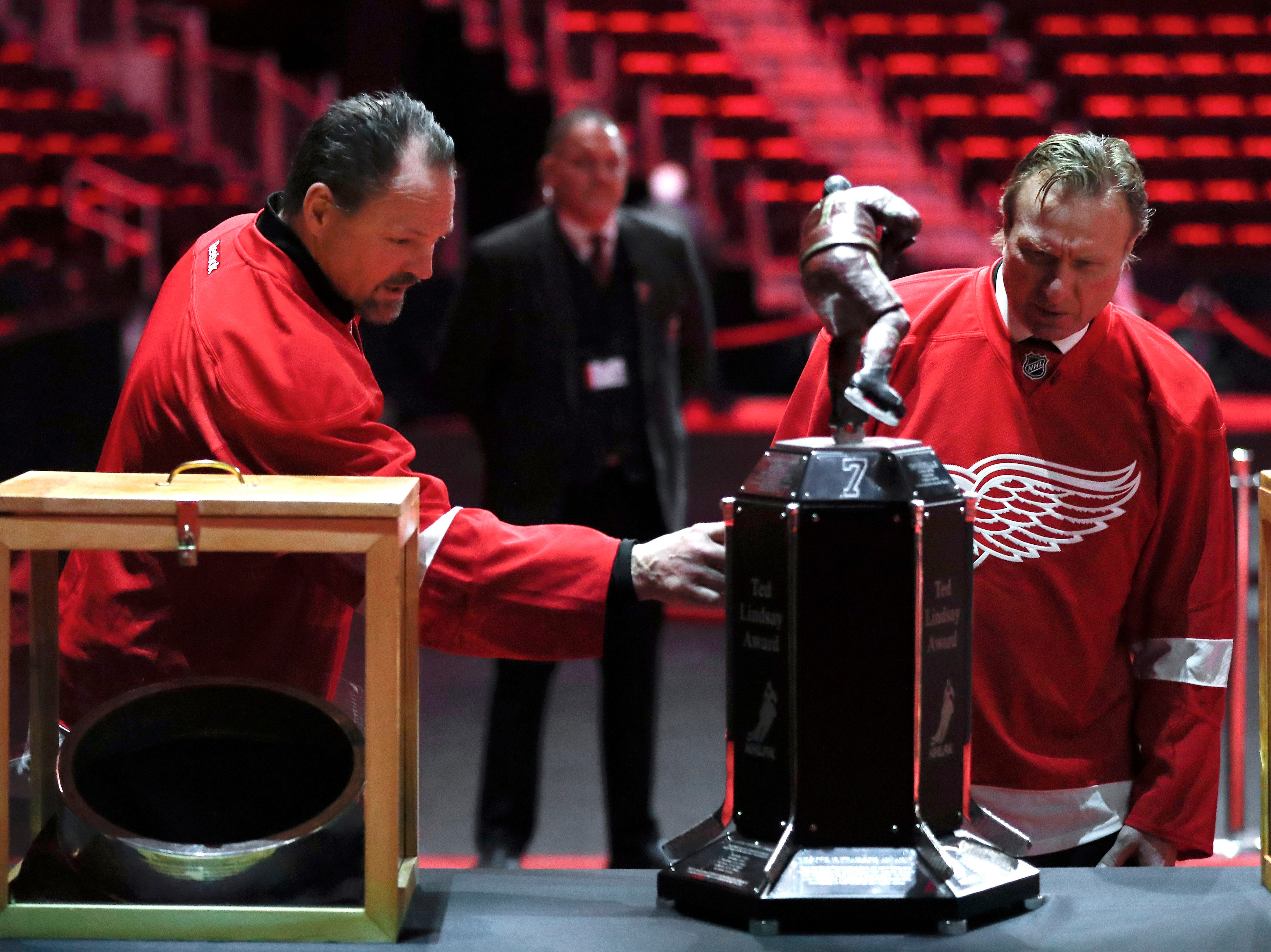 Former Detroit Red Wings players Joe Socur and Eddie Mio view memorabilia at the public viewing for Ted Lindsay.