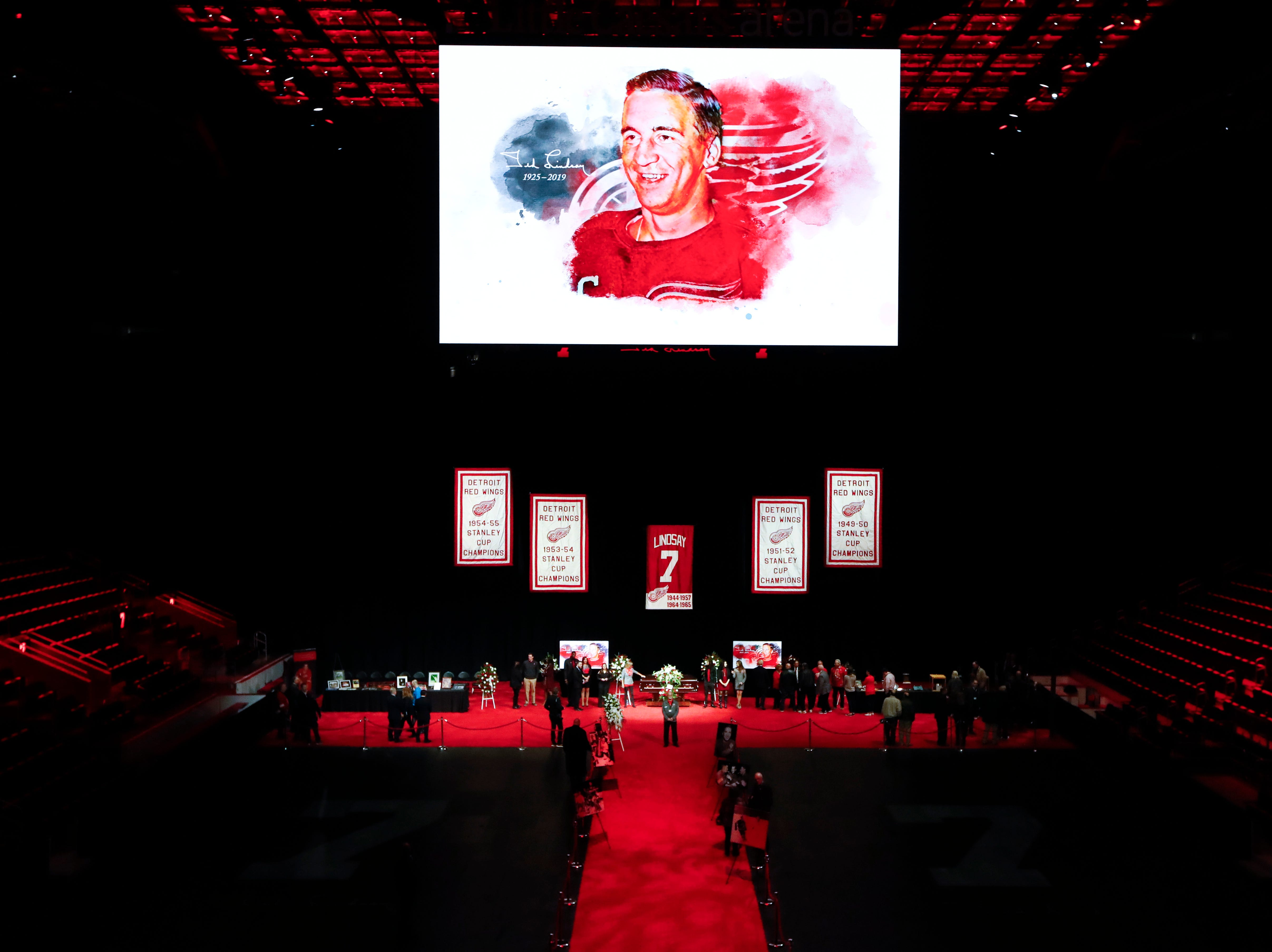 An illustration of Ted Lindsay is projected on the scoreboard as mourners view the casket in Little Caesars Arena.