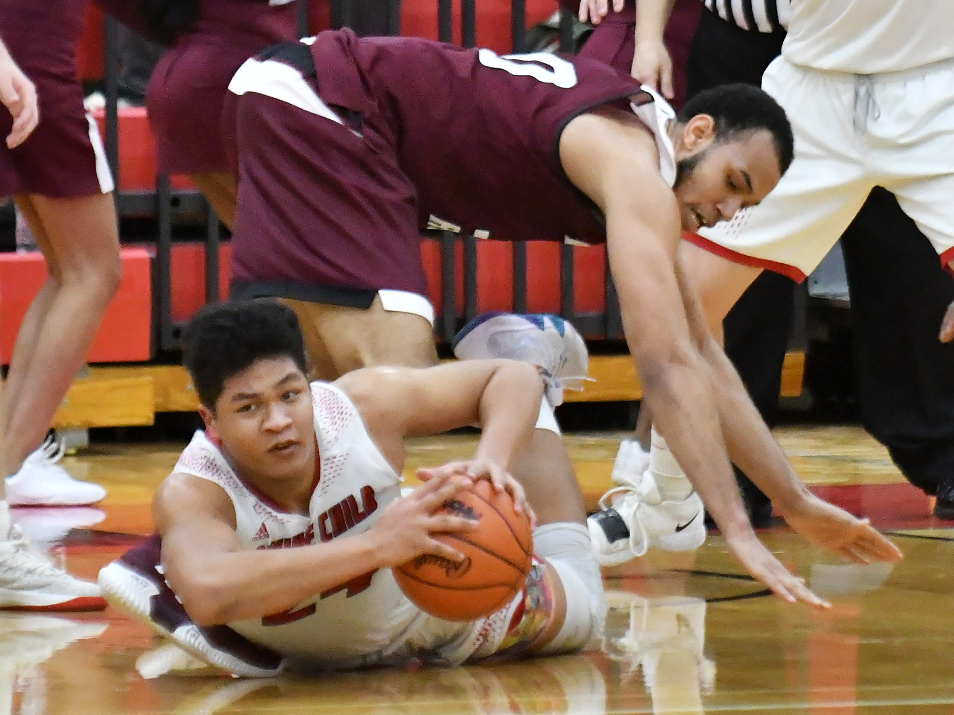 Divine Child's Aeron Latham, bottom, comes up with the ball under River Rouge's Dan Few in the second half.