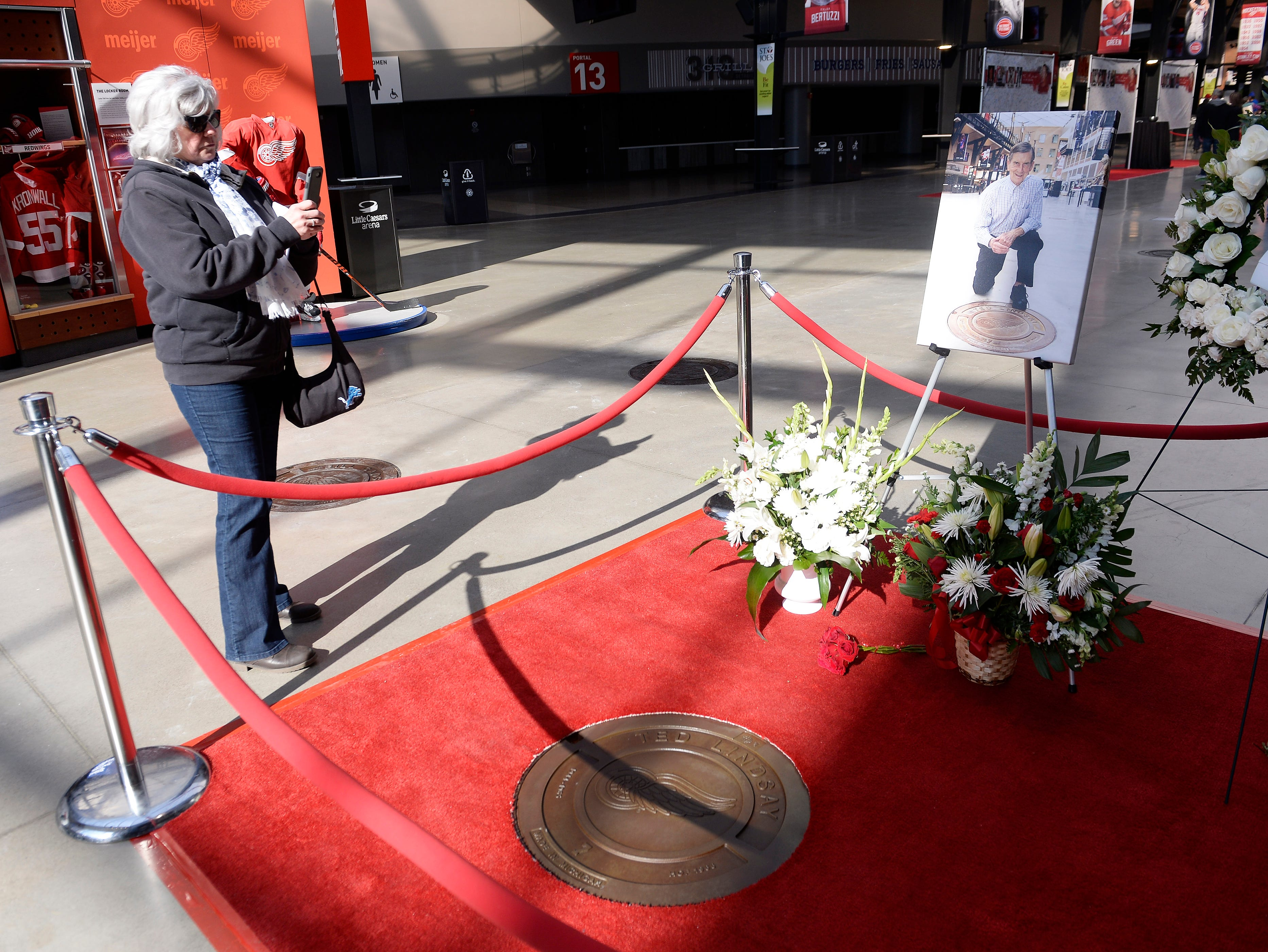 Barbara O'Connor, 61, of Dearborn takes a photo of the Ted Lindsay's commemorative manhole cover at Little Caesars Arena, one of several paying tribute to great players of the past.