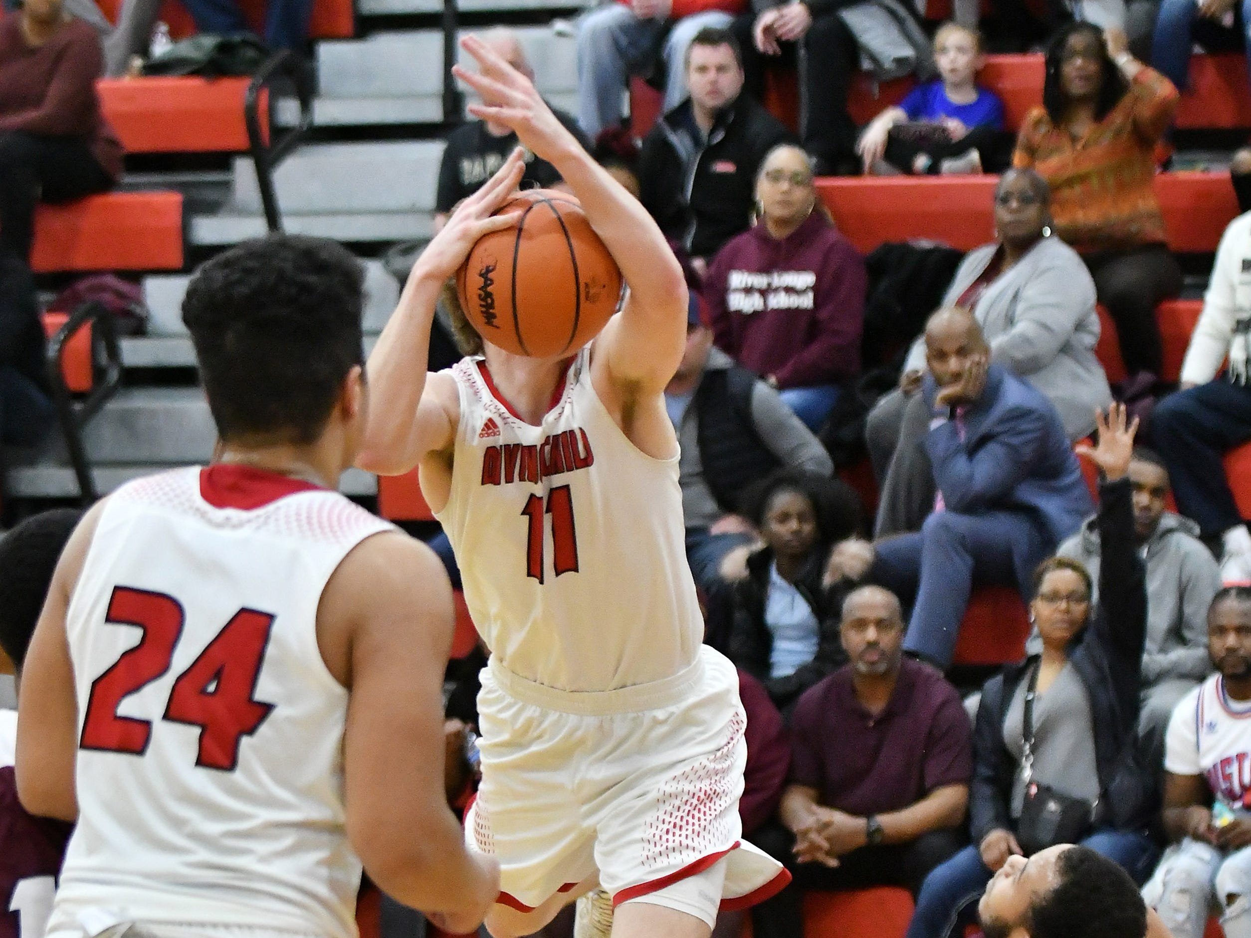 River Rouge's Dan Few is called for a blocking foul on this play with Divine Child's Kyle Gurney (11) in the first half.