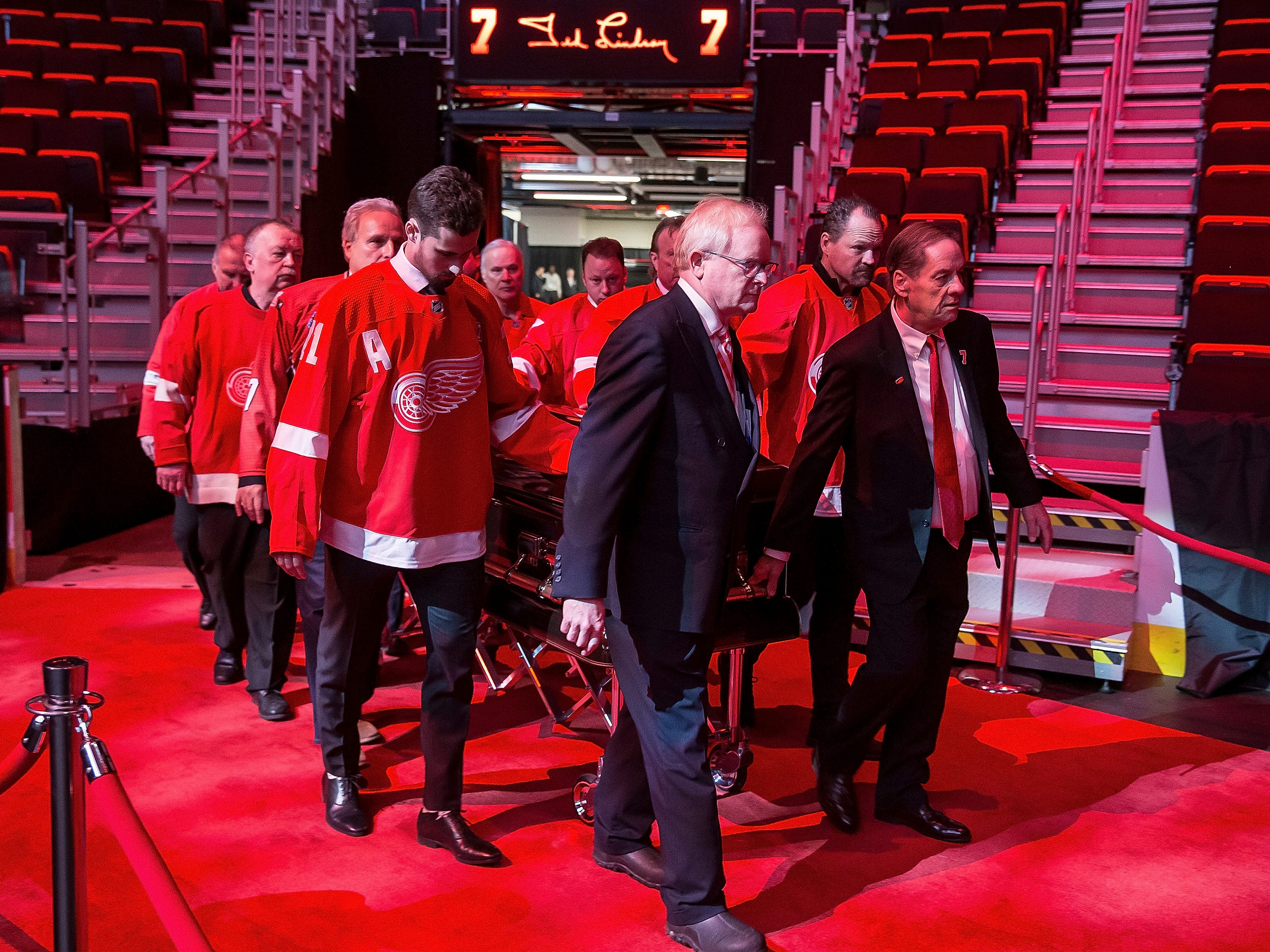 Blake Lindsay, right, son of Ted Lindsay, leads the casket of former Detroit Red Wing Ted Lindsay into the arena.