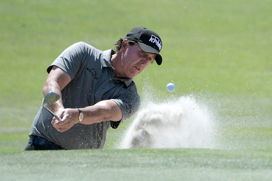 Phil Mickelson hits out of a bunker onto the second green.