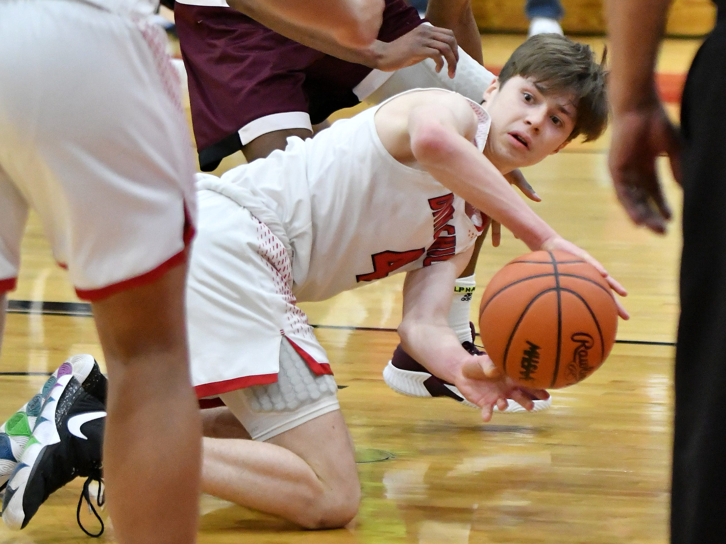 Divine Child's Parker LePage tries to pass while on his knees in the first half.
