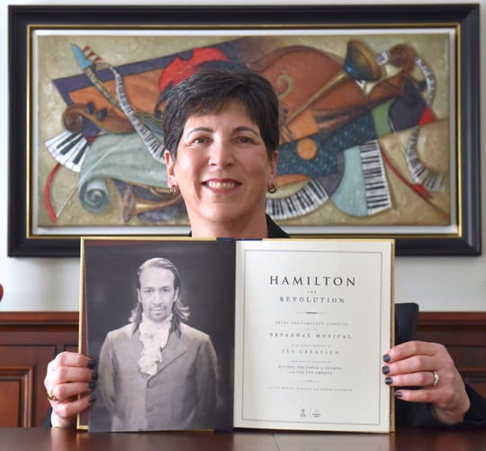 """Tracey Goddeeris, 60, poses with her book, """"Hamilton"""" The Revolution,"""" written by musical lead Lin-Manuel Miranda and Jeremy McCarter, at her Birmingham residence"""