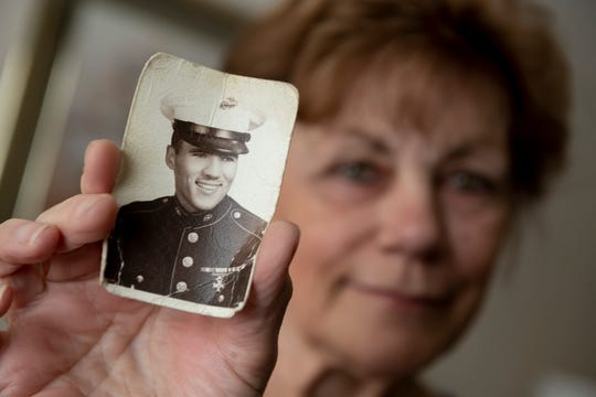 Lorraine Johnson holds a photograph of her late brother, Michael Bard, a lance corporal in the U.S. Marines, in her Dearborn Heights home.