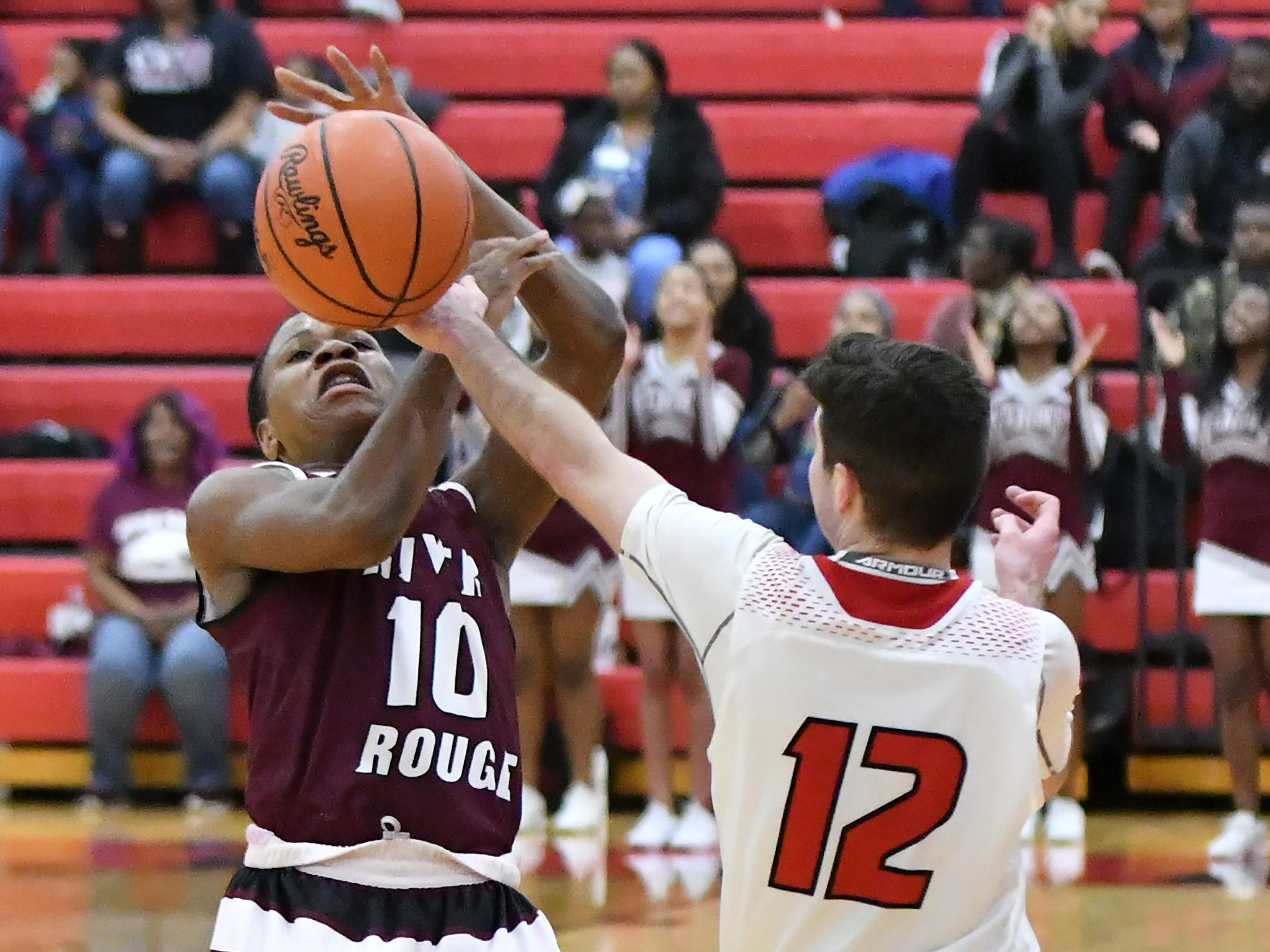 Divine Child's Jack Kenney (12) tries to steal the ball from River Rouge's Bralin Toney (10) in the first half.