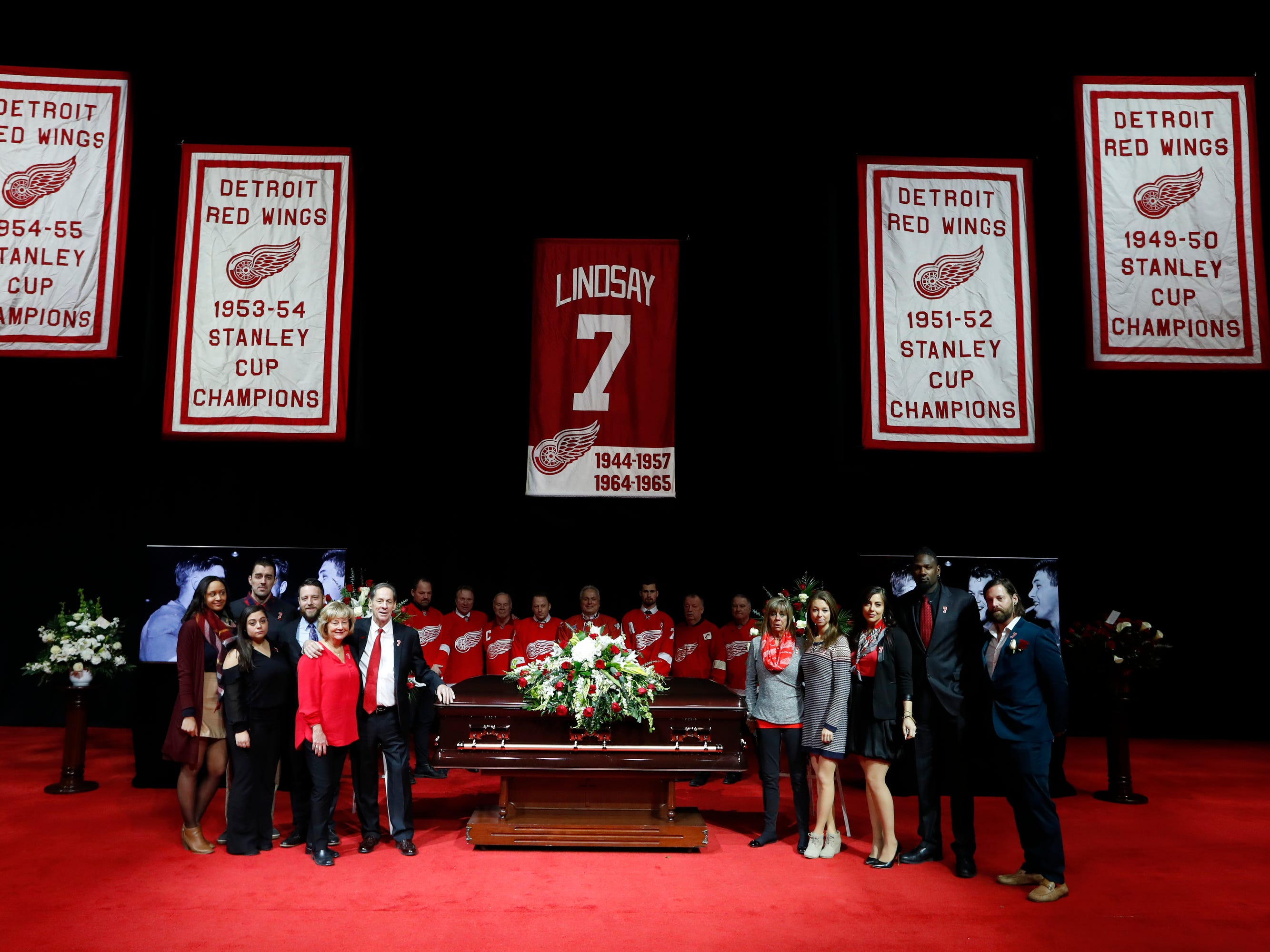 Family members pose with the casket of former Red Wing Ted Lindsay, with pallbearers behind it,  before the  public viewing. Lindsay's retired number hangs above.