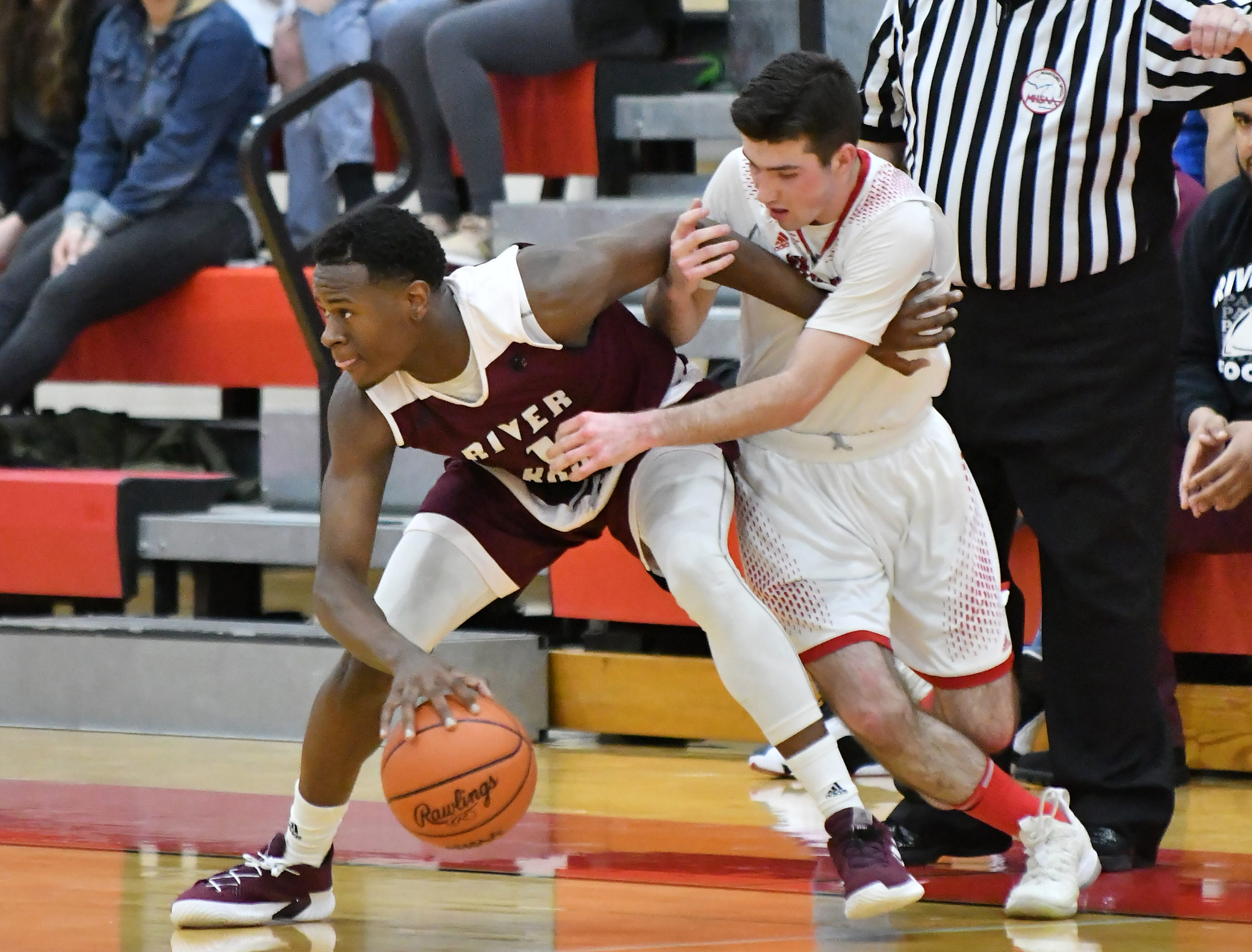 Divine Child's Jack Kenney, right, guards River Rouge's Donovan Freeman in the first half.