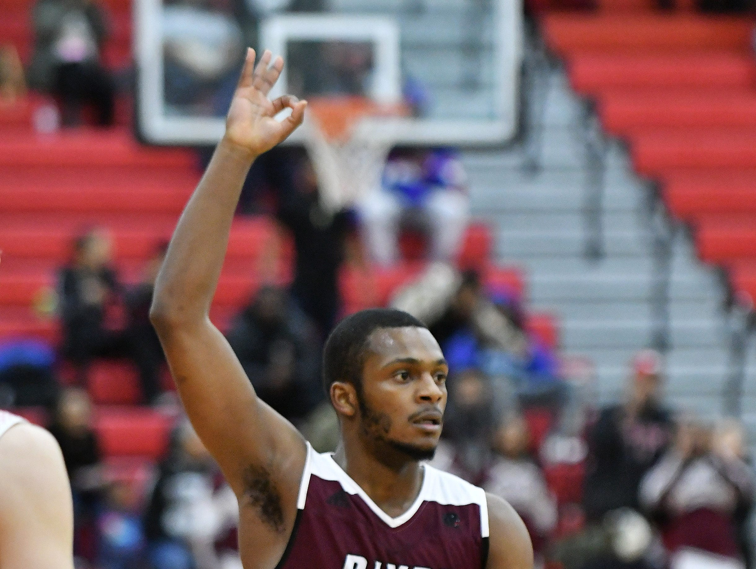 River Rouge's Nigel Colvin signals a made three-point shot in the first half.