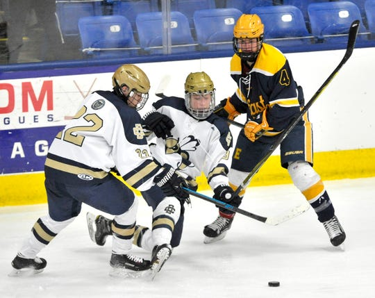 Country Day's Lucas Krol, fromleft, and Logan Gotinsky battle East Grand Rapids' Nate Milanowski during the second period at USA Hockey Arena in Plymouth on Friday.