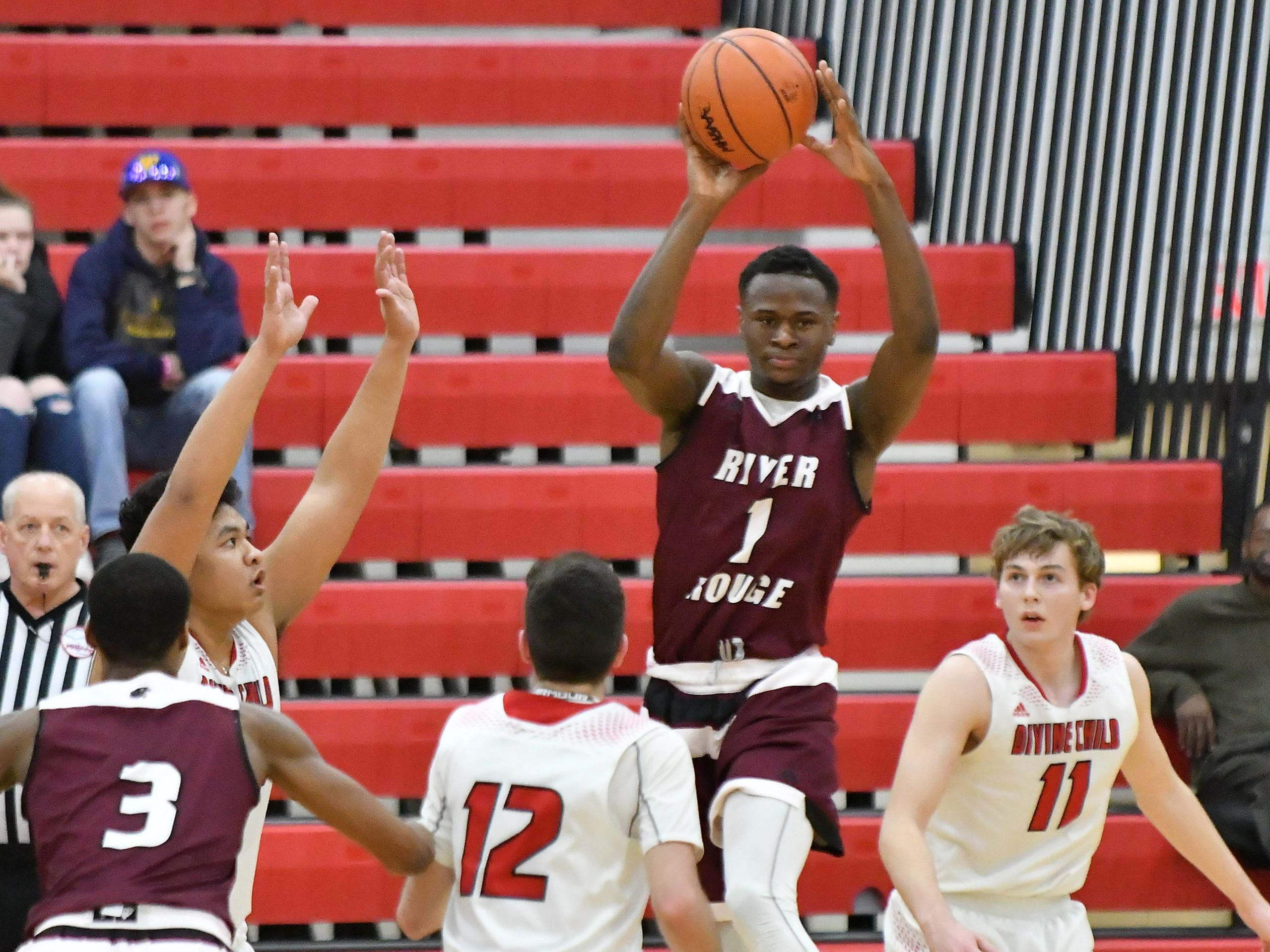 River Rouge's Donovan Freeman (1) passes over Divine Child defenders  Aeron (cq) Latham, Jack Kenney (12) and Kyle Gurney (11) in the first half.