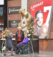 Kathy Best, right,  of Westland, and her friend, Dennis Davidson, of Belleville, have their picture taken by Grace Fenton  of Grosse Pointe Park in front of the Ted Lindsay statue at Little Caesars Arena Friday. Best worked in media relations for the Red Wings and for Lindsay when he was GM of the team. Davidson worked as the press box public address announcer at both Olympia Stadium and Joe Louis Arena.