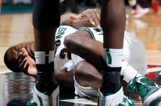 Michigan State's Branden Dawson lies on the court after going down with an injured left knee during the first half on March 4, 2012.
