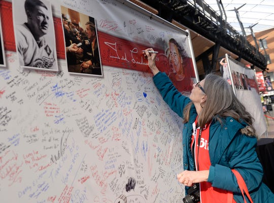Diane Grover, 68, of Ferndale signs one of the white board cards on display inside Little Caesars Arena.