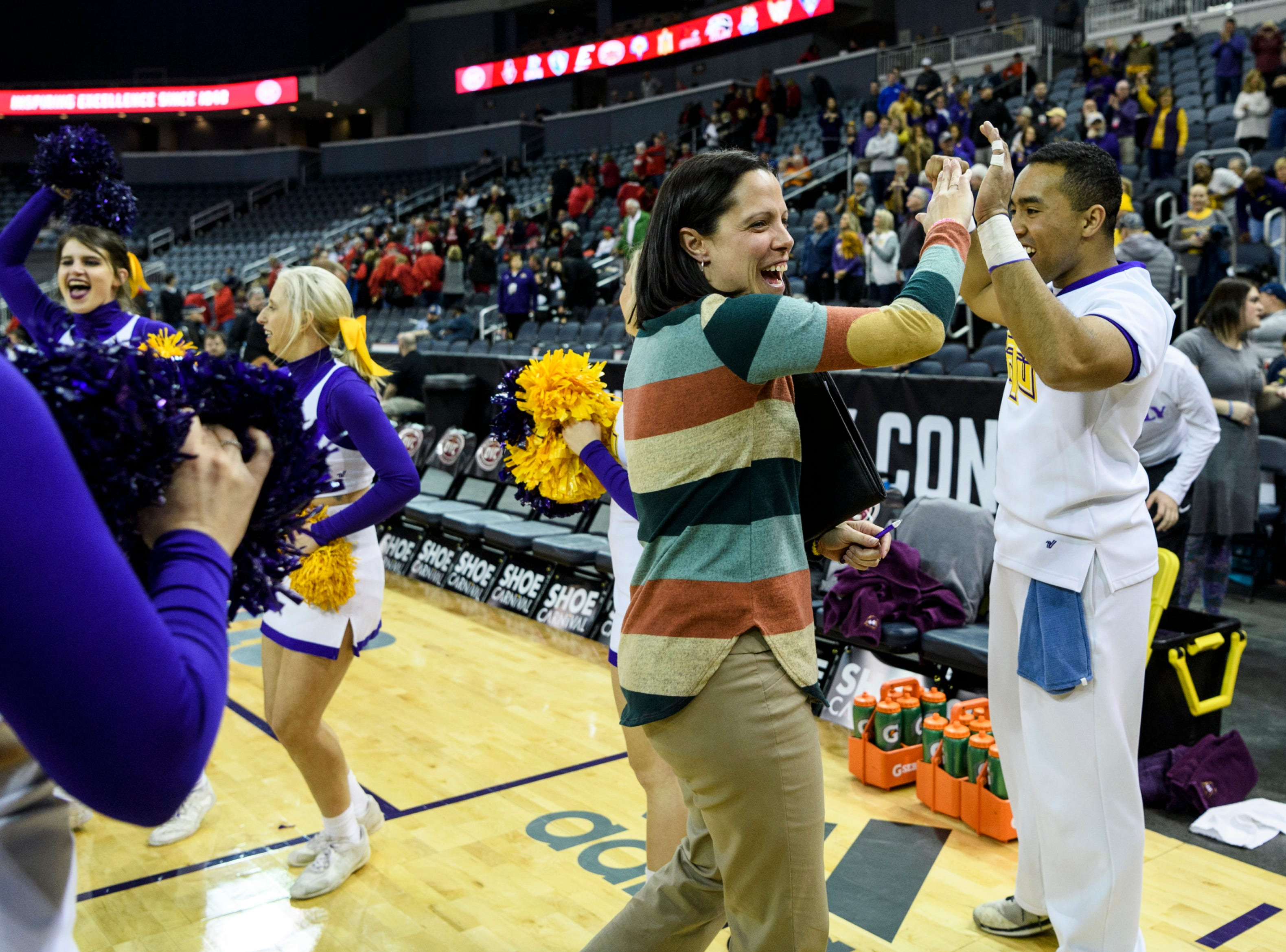 Allison Clark, center, assistant coach for the women's Tennessee Tech basketball team, high-fives the cheerleading team as they celebrate their win over Austin Peay Governors during the Ohio Valley Conference tournament at Ford Center in Evansville, Ind., Thursday, March 7, 2019. The Golden Eagles defeated the Governors, 69-57.