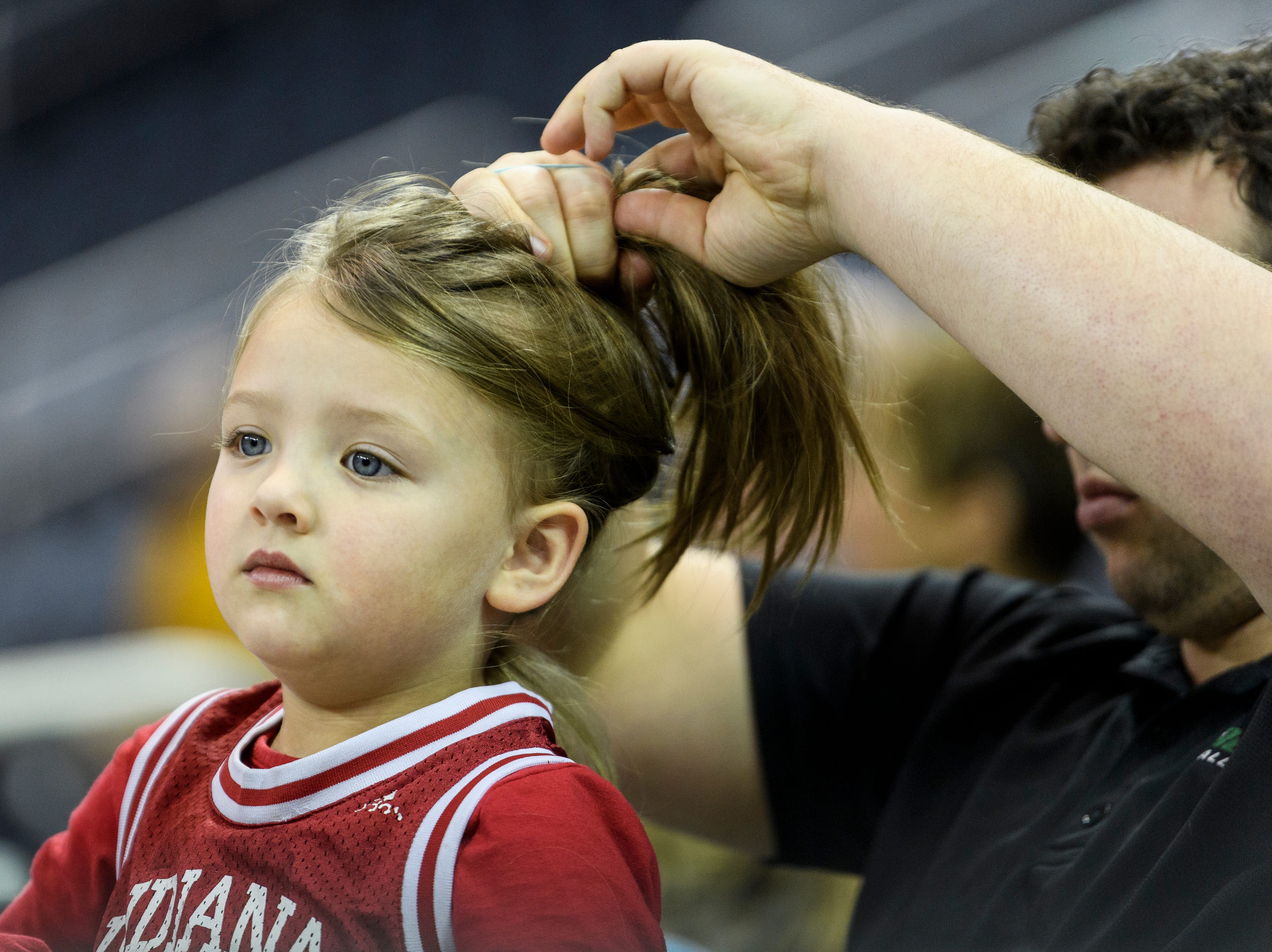 Johnathan Henton of Albion, Ind., helps his daughter Charley Henton, 5, put her hair in a bun as they watch the Ohio Valley Conference men's and women's basketball tournament at Ford Center in Evansville, Ind., Thursday, March 7, 2019. Charley and her older sister Adyson, 7, not pictured, like to play and watch basketball.