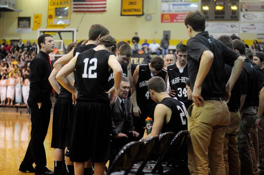 "Barr-Reeve coach Bryan Hughes, center, knells in a huddle of his players during a timeout of a game that the small high school played at Loogootee High School's gym during the 2014-15 season that is documented in the documentary movie ""Kings of Indiana."""