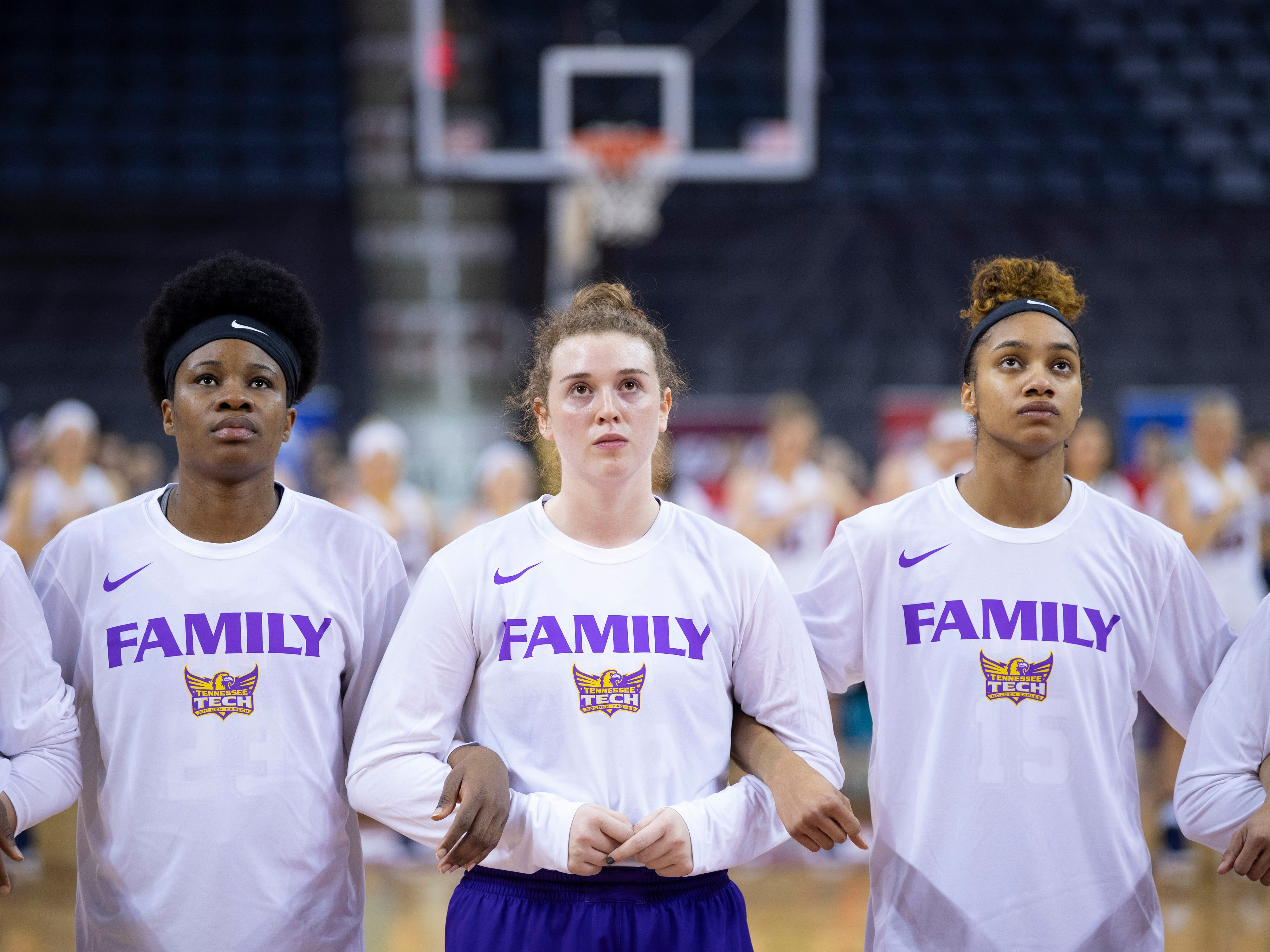 Tennessee Tech's Peace Okeke, left, Hannah Garrett, center, and Anacia Wilkinson link arms with their Golden Eagles teammates for the playing of The Star-Spangled Banner before their Ohio Valley Conference game against the Belmont Bruins at the Ford Center Friday afternoon.