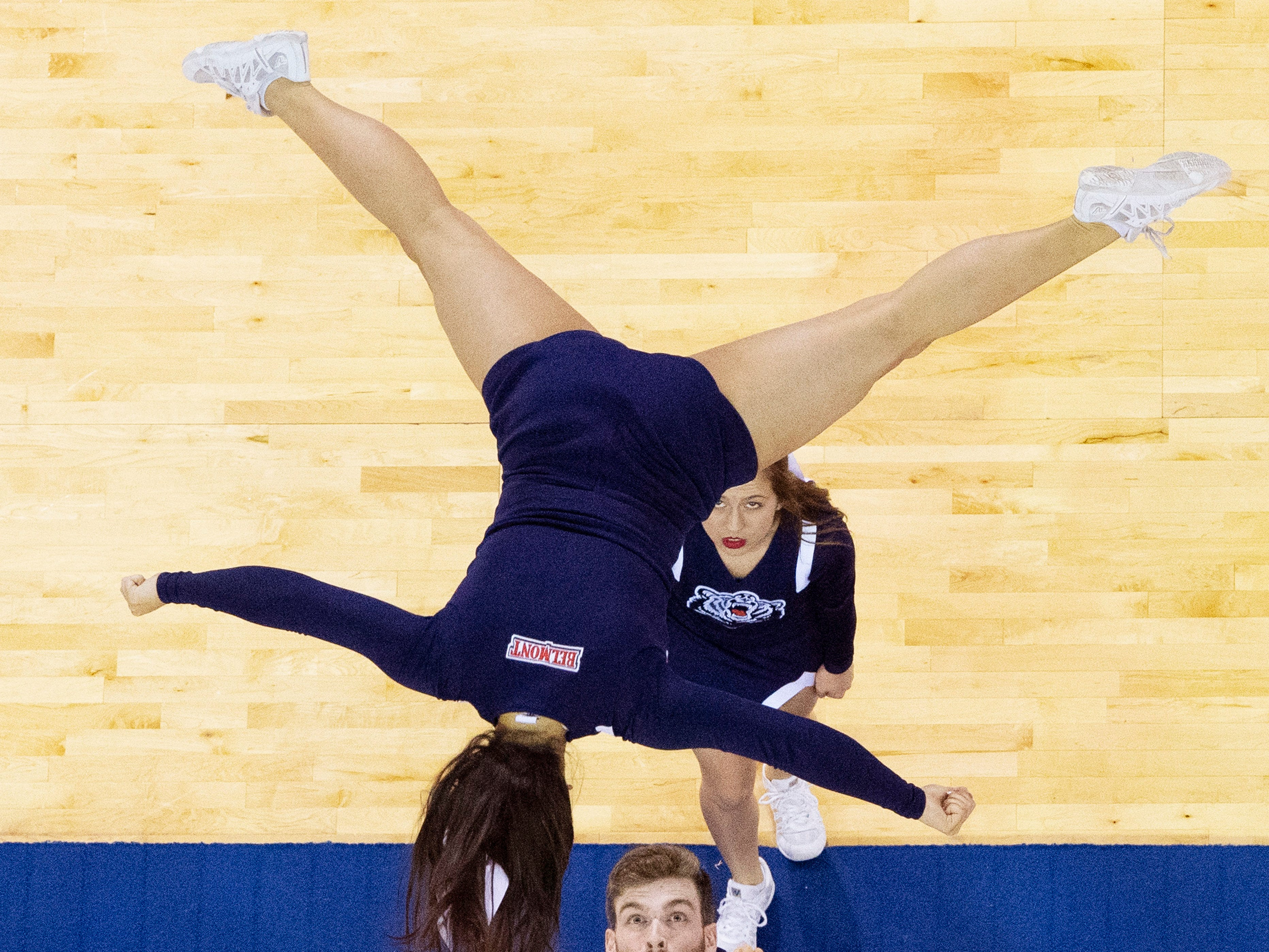 The Belmont Cheerleaders look to catch their flyer during a halftime performance at the Ford Center in Evansville Friday afternoon. The Belmont Bruins women's basketball team beat the Tennessee Tech Golden Eagles in the semifinal game of the Ohio Valley Conference Basketball Championships.