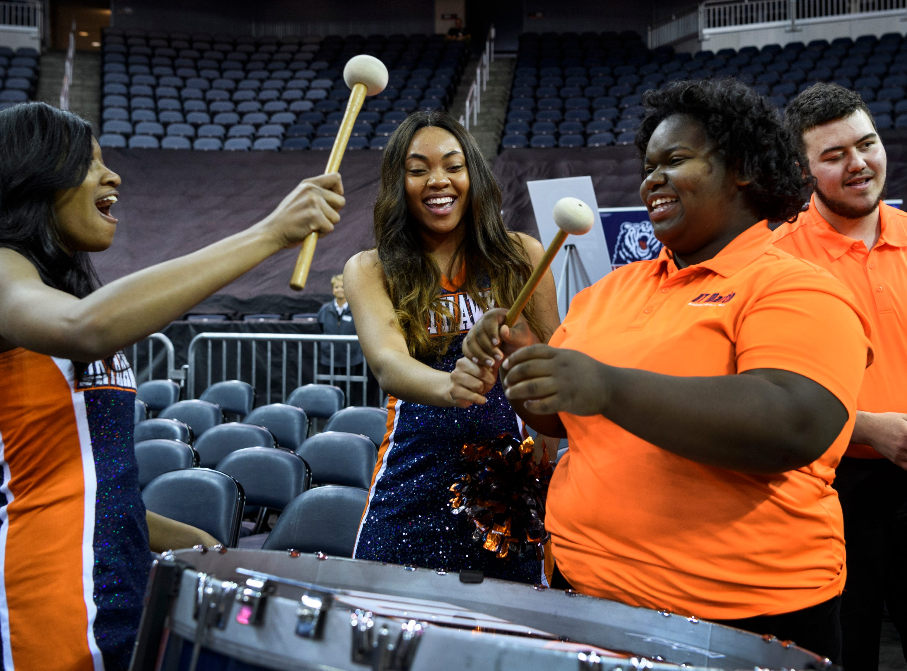 Dancers Jamesha Shelton and Lindsay Williams beat on a drum with Brianna Hampton, a member of the University of Tennessee Martin pep band, during the women's game against Murray State at the Ohio Valley Conference tournament in Evansville's Ford Center, Thursday, March 7, 2019.