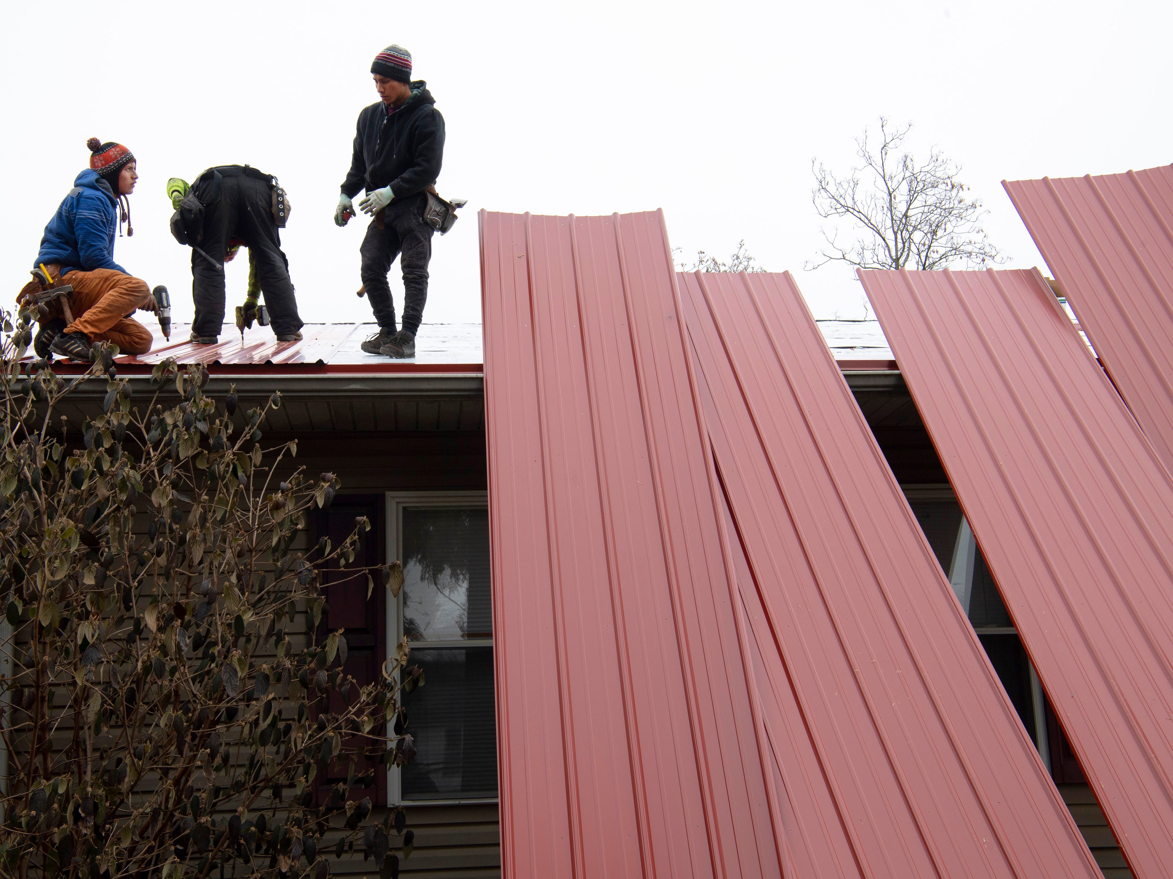 Roofers take advantage of a break in the weather to install steel roofing panels onto a North Side Evansville home Friday morning. The roofers, from left, Harley Matias, Jason Norton and Delmar Matias would be finished with the job by knock-off.