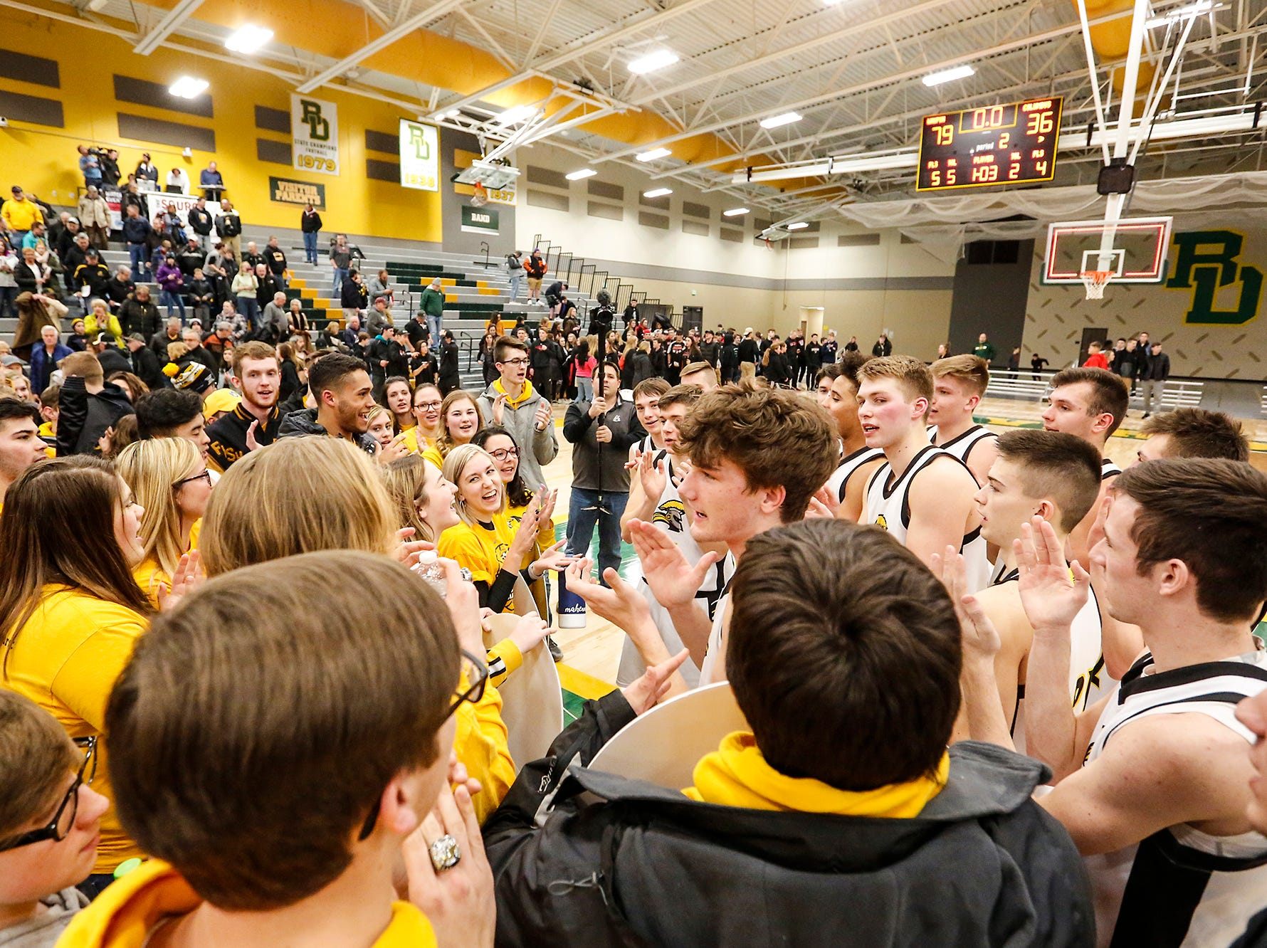 Waupun High School boys basketball players celebrate with Waupun students after their WIAA division 3 sectional semi-final game against Columbus High School Thursday, March 7, 2019 in Beaver Dam, Wis. Waupun won the game 79-36. Doug Raflik/USA TODAY NETWORK-Wisconsin