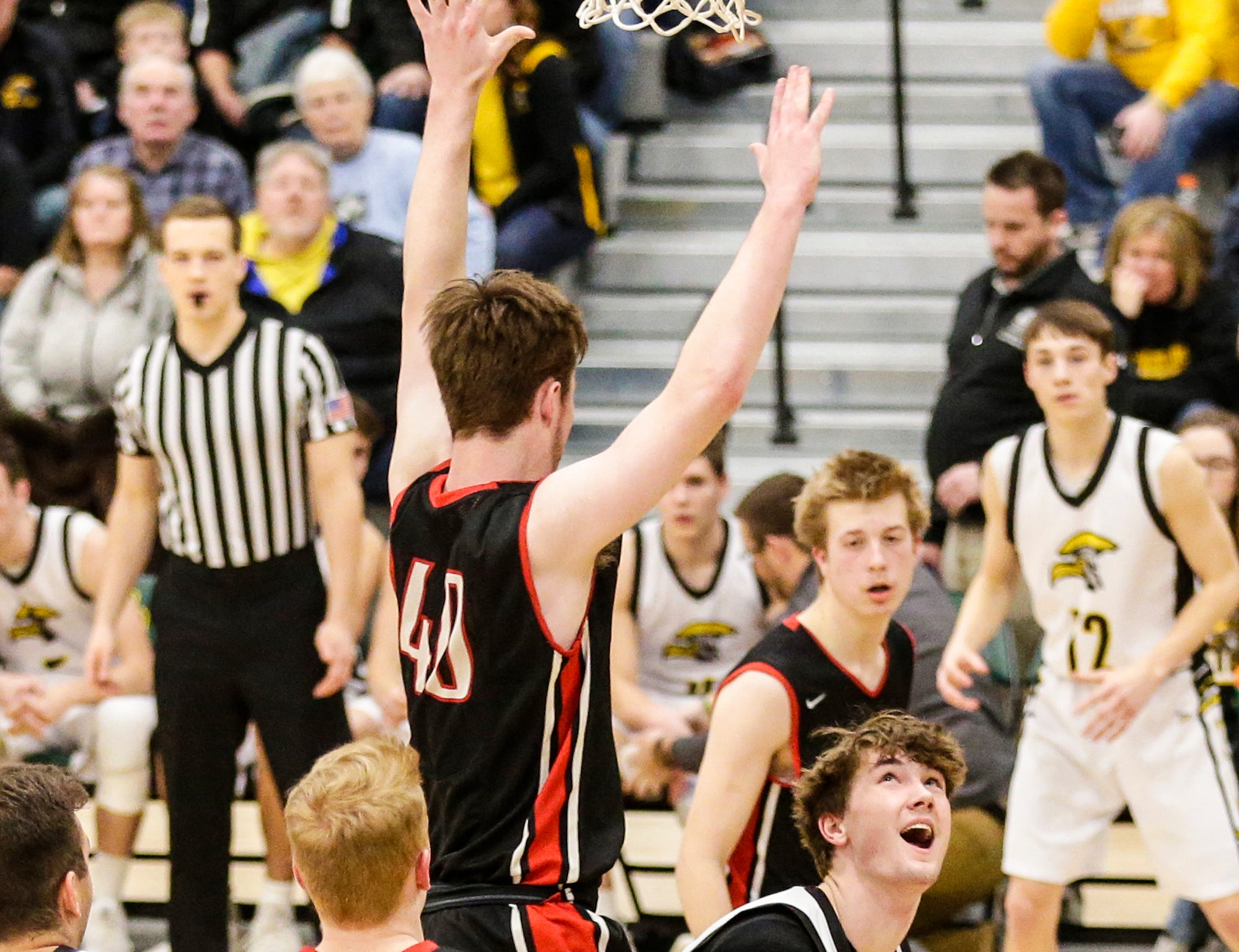 Waupun High School boys basketball's Reece Homan (23) eyes up the basket under Columbus High School's Ben Emler (40) during their WIAA division 3 sectional semi-final game Thursday, March 7, 2019 in Beaver Dam, Wis. Waupun won the game 79-36. Doug Raflik/USA TODAY NETWORK-Wisconsin