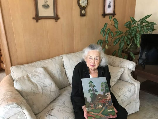 Sitting below portraits of her family members, Evelyn Beck holds the painting she purchased from a German POW while working in the same Pickett canning factory in 1944.