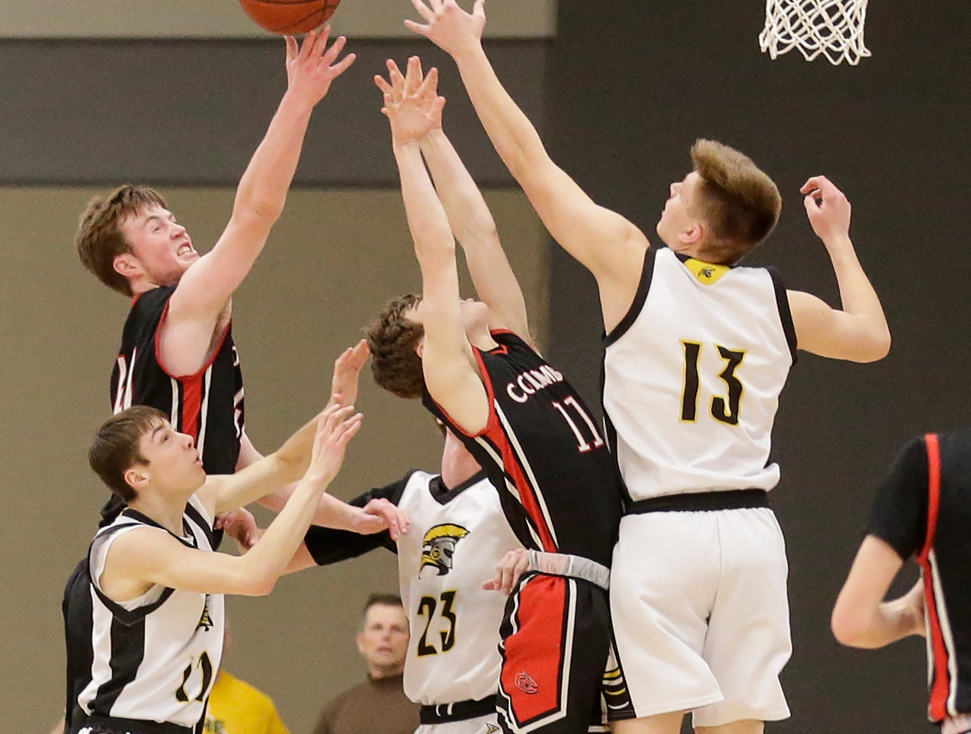 Waupun High School boys basketball's Gabe Keach (21) Reece Homan (23) and Conner Kamphuis (13) battle for a rebound with Columbus High School's Teagan Herschleb (21) and Alex Campbell (11) during their WIAA division 3 sectional semi-final game Thursday, March 7, 2019 in Beaver Dam, Wis. Waupun won the game 79-36. Doug Raflik/USA TODAY NETWORK-Wisconsin