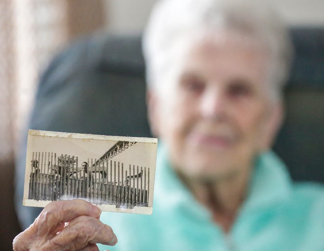 Gloria Lettau of Fond du Lac holds up a photo she took of German POWs while they were held during WWII at the Fond du Lac Fairgrounds.